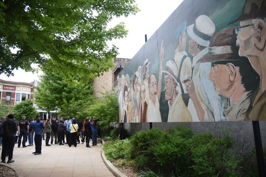 Protesters gather Friday on a pedestrian walkway between Spring Street and Grove Avenue in Elgin by an Elgin mural that portrays an iconic 1930 photo of a lynching of two black men in Indiana. The city decided to move the mural indoors to the Hemmens Cultural Center.