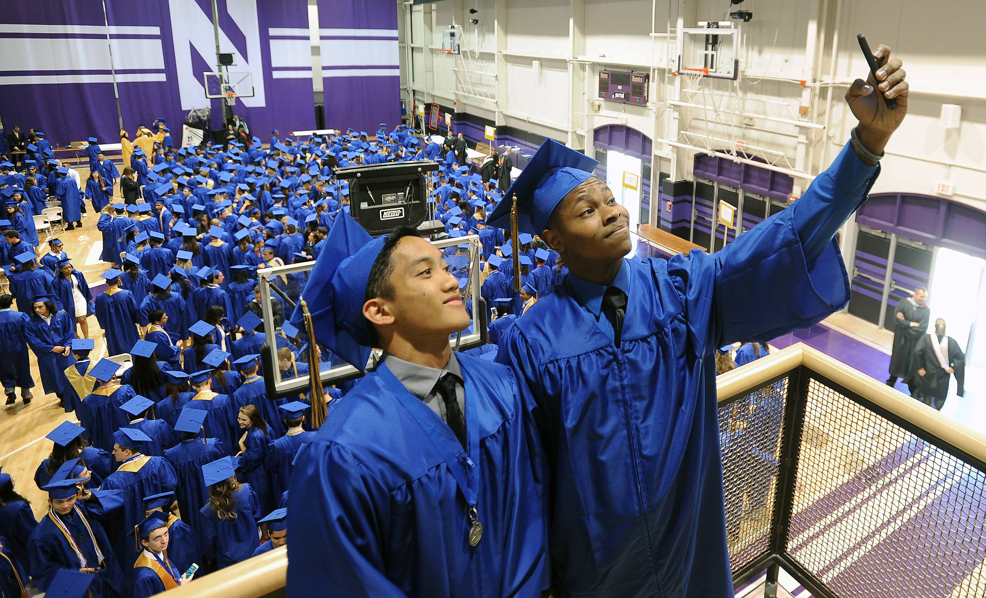 Eric Ablang, 18, of Gurnee and Carl Fleming, 18, of Gurnee take a selfie with their classmates behind them at Warren Township High School's 99th commencement ceremony Saturday at Welsh-Ryan Arena at Northwestern University in Evanston.