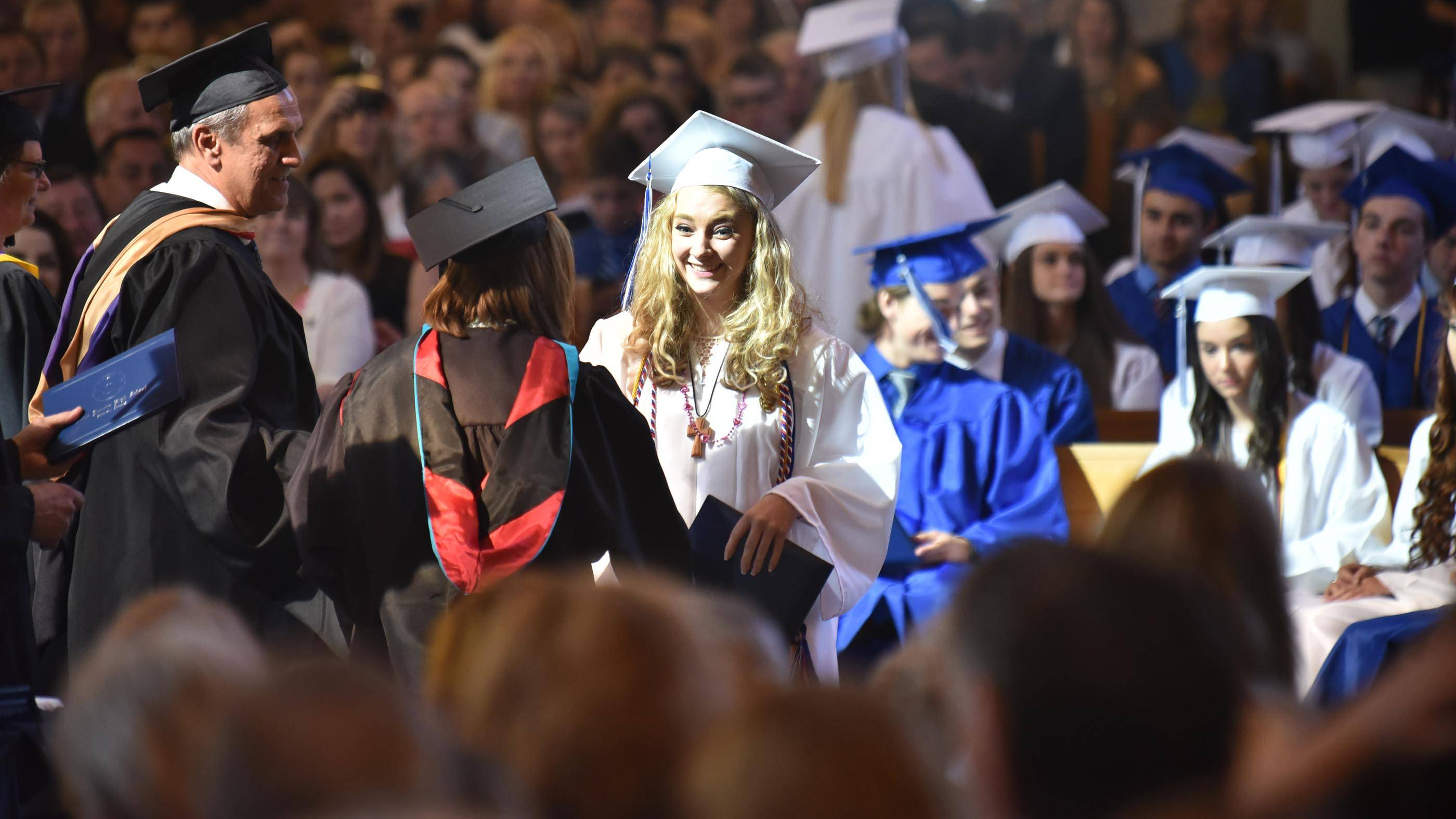 Graduate Kathleen Kleve smiles as she accepts her diploma at the St. Francis High School graduation Sunday at St. John Neumann Church in St. Charles.