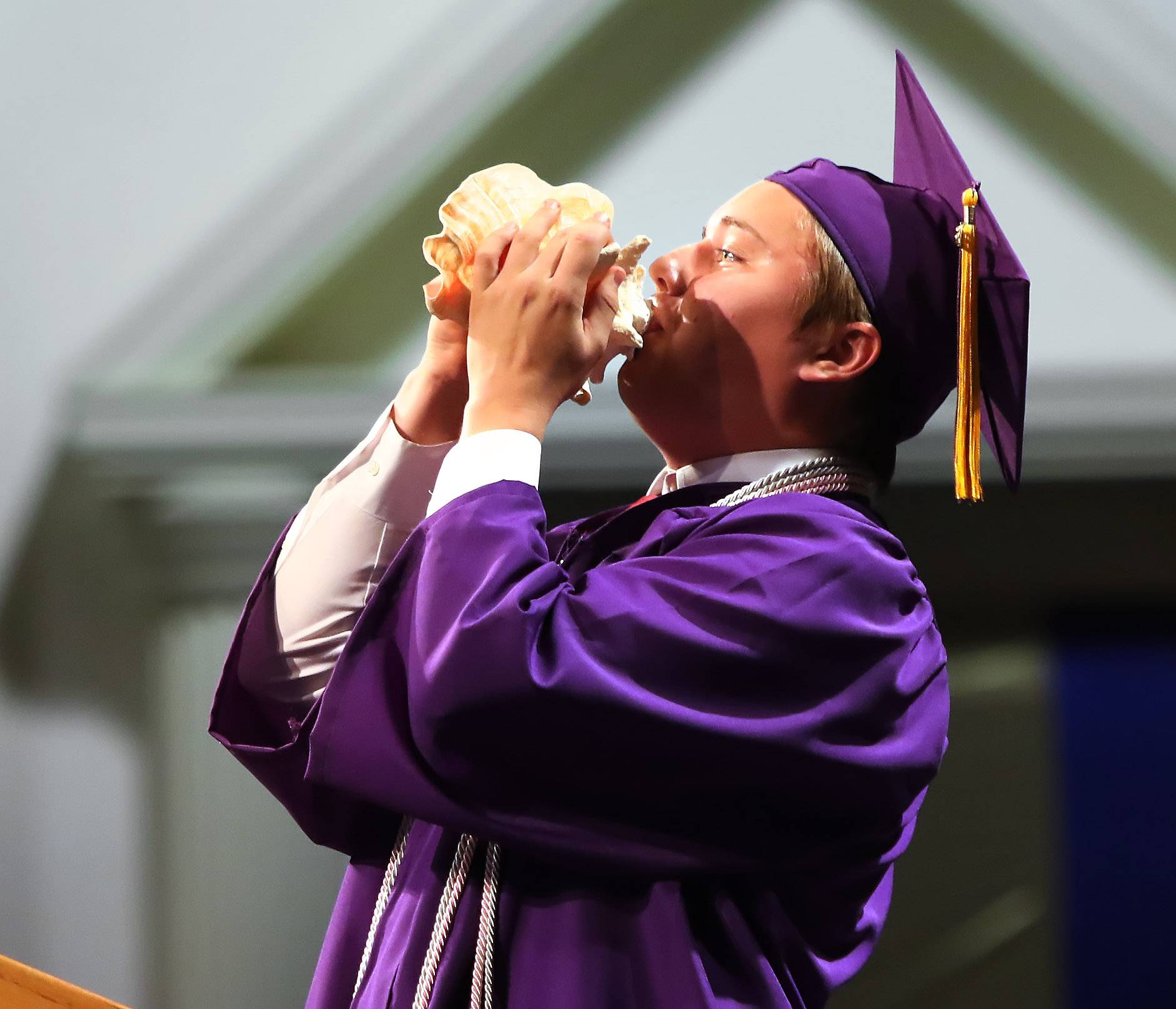 Class representative John Farwick blows into a conch shell after his speech during the Wauconda High School graduation ceremony on Sunday at Quentin Road Bible Church in Lake Zurich. There were 359 graduates during the 100th annual commencement ceremony.