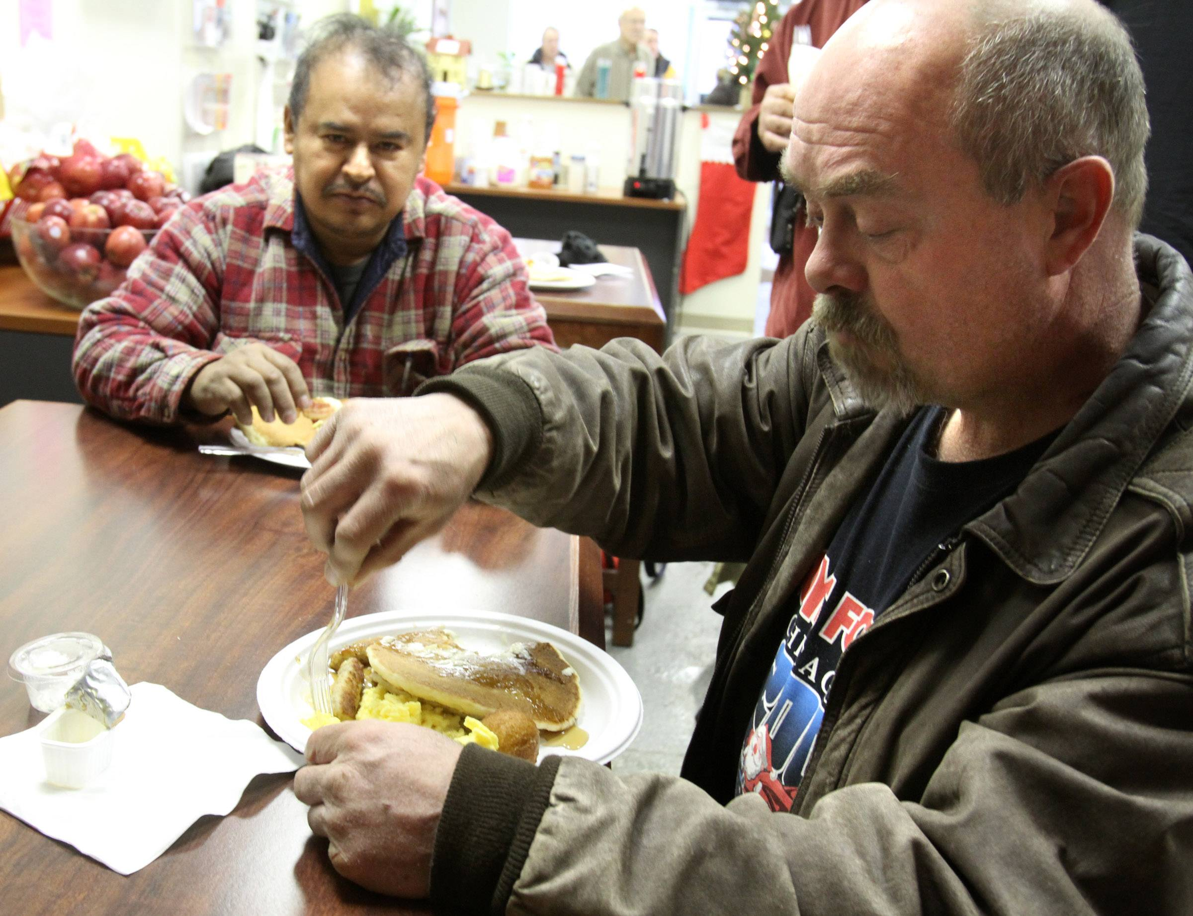 Men eat a pancake breakfast at Journeys in Palatine. Agency leaders say federal cuts could end their transitions program that helps homeless people in the suburbs get back on their feet.