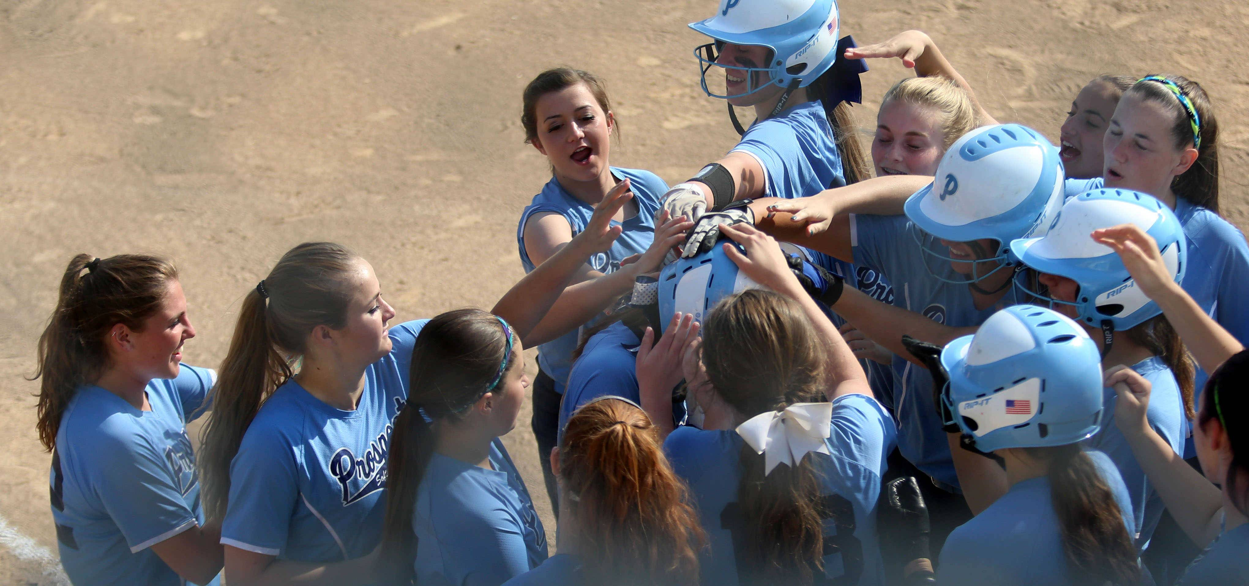 Prospect greets Alyssa Cacini after her second home run of the day against Lake Forest during softball playoff action in Mt. Prospect on Monday.