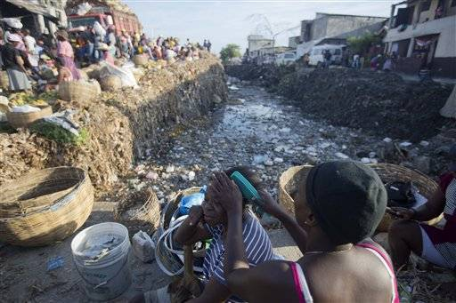 In this Saturday, May 21, 2016 photo, a vendor combs another woman's hair next to a water canal full of rubbish, fertile ground for mosquito-borne diseases, near a street market in Port-au-Prince, Haiti. Haiti's government has stepped up fumigation and public service announcements about the importance of getting rid of mosquito breeding grounds, but mosquito control is minimal compared to more developed nations. (AP Photo/Dieu Nalio Chery)