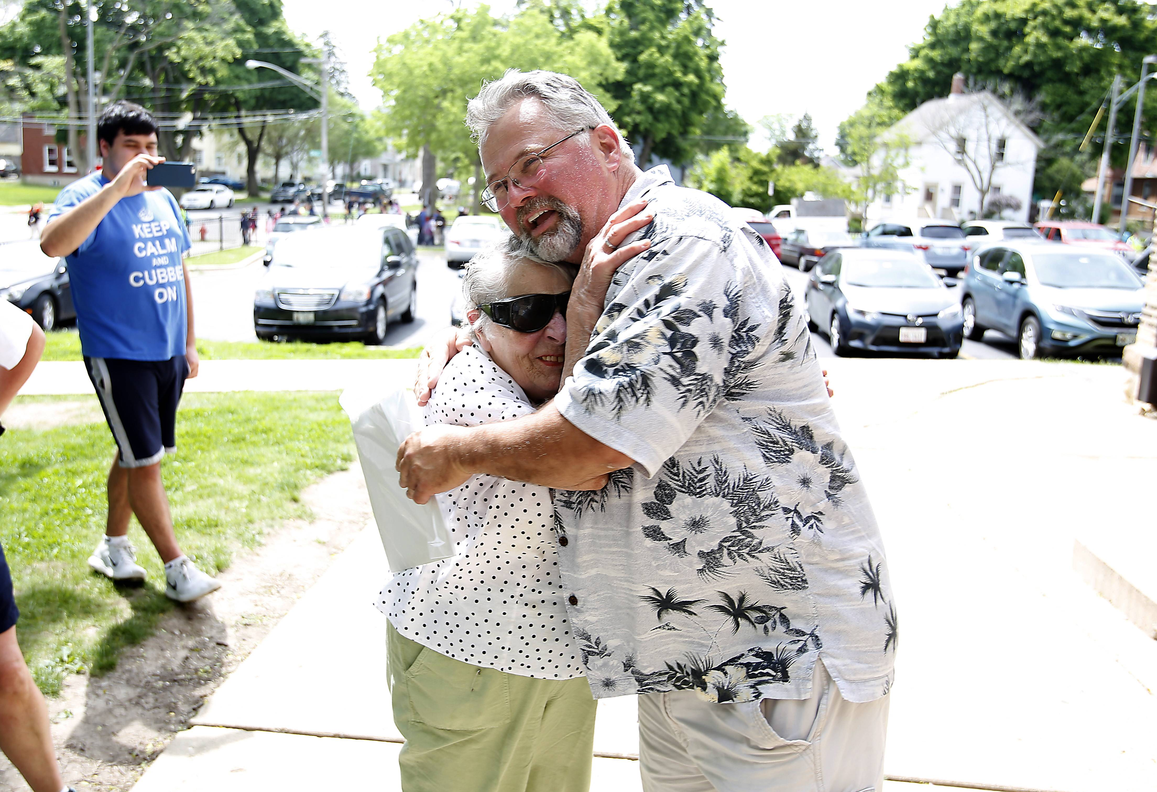 Gordon Whiting, an Elgin High School social studies teacher and alum, gets a big hug Wednesday from his mom, Janet, after he exited through the same door at Garfield Elementary School in Elgin where he attended kindergarten.