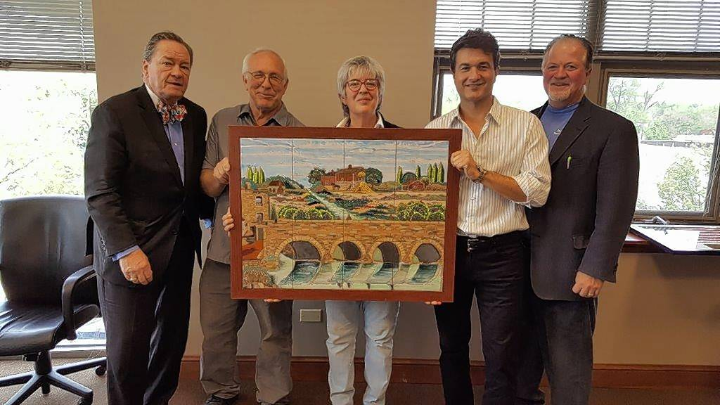 Artist Debora Duran-Geiger, center, displays a small version of one of five ceramic murals she will create for installation at the new Water Street District in downtown Naperville. With her are, from left, Brand Bobosky, chairman of the Century Walk Corp. public art nonprofit; her husband Michael Geiger; Peter Foyo, who has invested in the art; and Nick Ryan, CEO of Water Street developer Marquette Companies, which also has invested in the pieces.