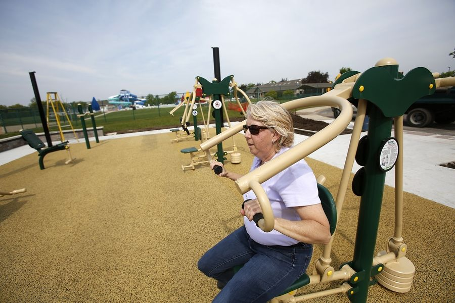 Huntley Park District recreation director Debbie Kraus tries out some equipment in a new outdoor fitness area in Deicke Park that is set to open June 12. It includes nine pieces of resistance and strength training equipment, some of which are accessible to people with disabilities.