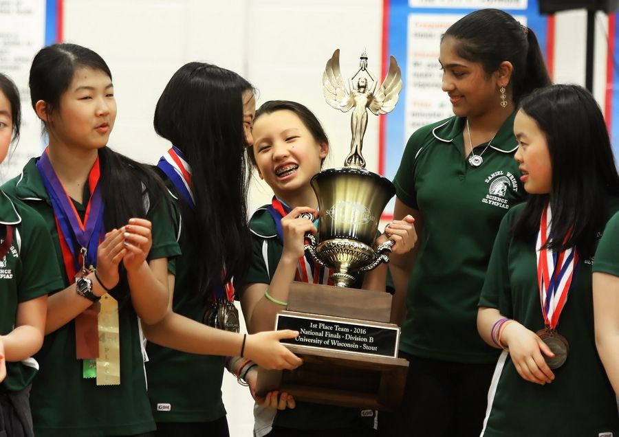 Wright Junior High School sixth-grader Anna Cai holds the trophy with help from Hannah Liu, left, during Wednesday's assembly to honor the Lincolnshire school's national champion Science Olympiad team. Mayor Elizabeth Brandt presented a proclamation for the team.