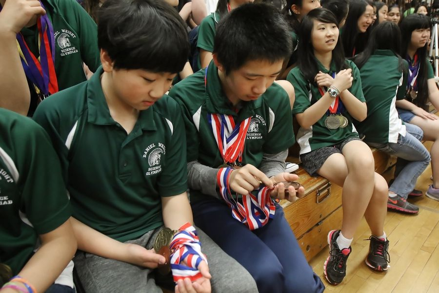 Wright Junior High School Science Olympiad team members Raymond Cao, left, and Eric Gan look at their medals during an assembly Wednesday at the Lincolnshire school to honor their national championship. It was the first Science Olympiad national championship for an Illinois school.