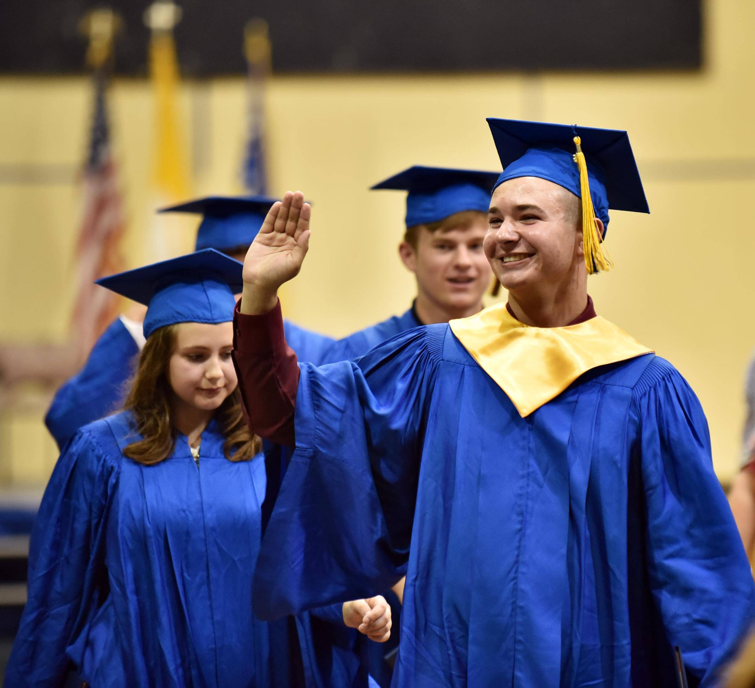 Graduate Andrew Alessia waves as he leaves the Aurora Central Catholic gymnasium Thursday following the 2016 commencement exercises.