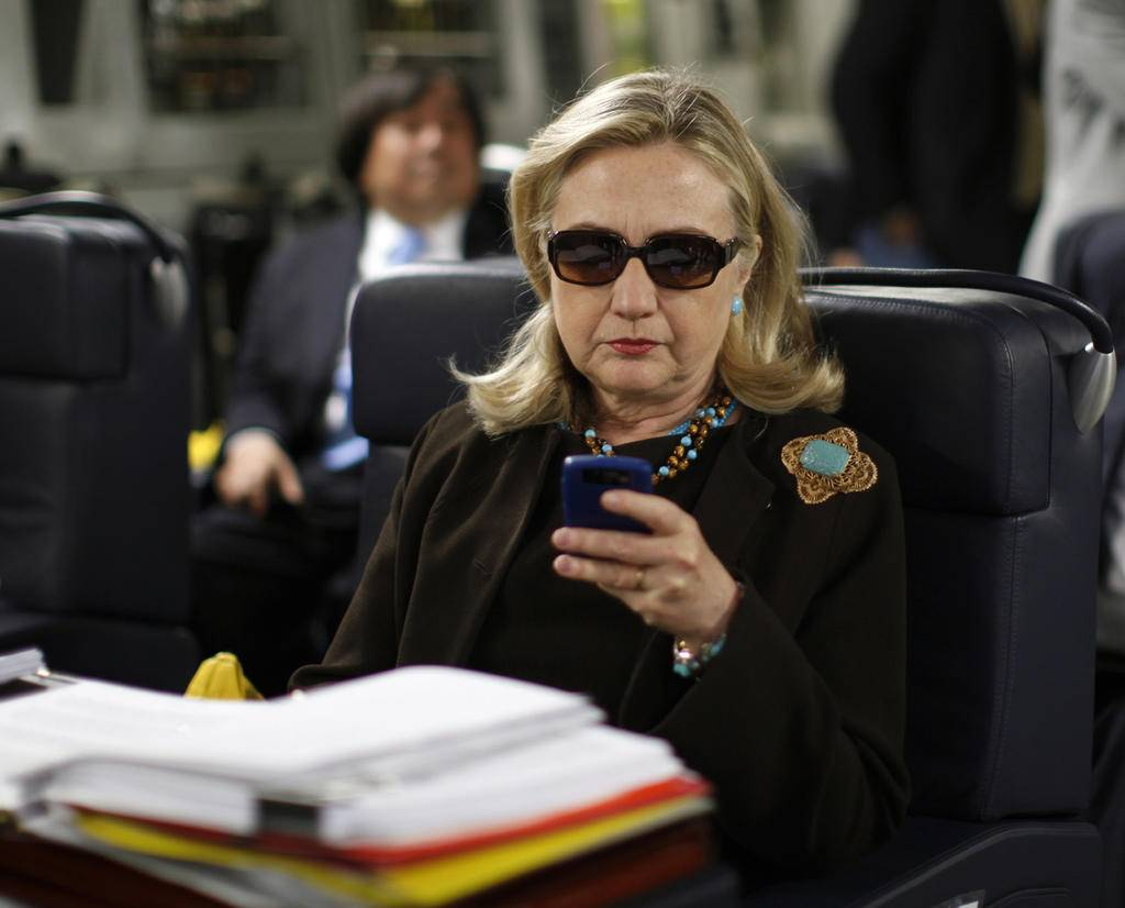 FILE - In this Oct. 18, 2011, file photo, then-Secretary of State Hillary Rodham Clinton checks her Blackberry from a desk inside a C-17 military plane upon her departure from Malta, in the Mediterranean Sea, bound for Tripoli, Libya.Clinton is telling voters not to trust Donald Trump, but a new government report about her usage of a private server as secretary of state is complicating that message. The sharp rebuke from the State Department's Inspector General, which found Clinton did not seek legal approval for her homebrew email server, guarantees that the issue will remain alive and well for the likely Democratic presidential nominee. (AP Photo/Kevin Lamarque, Pool, File)