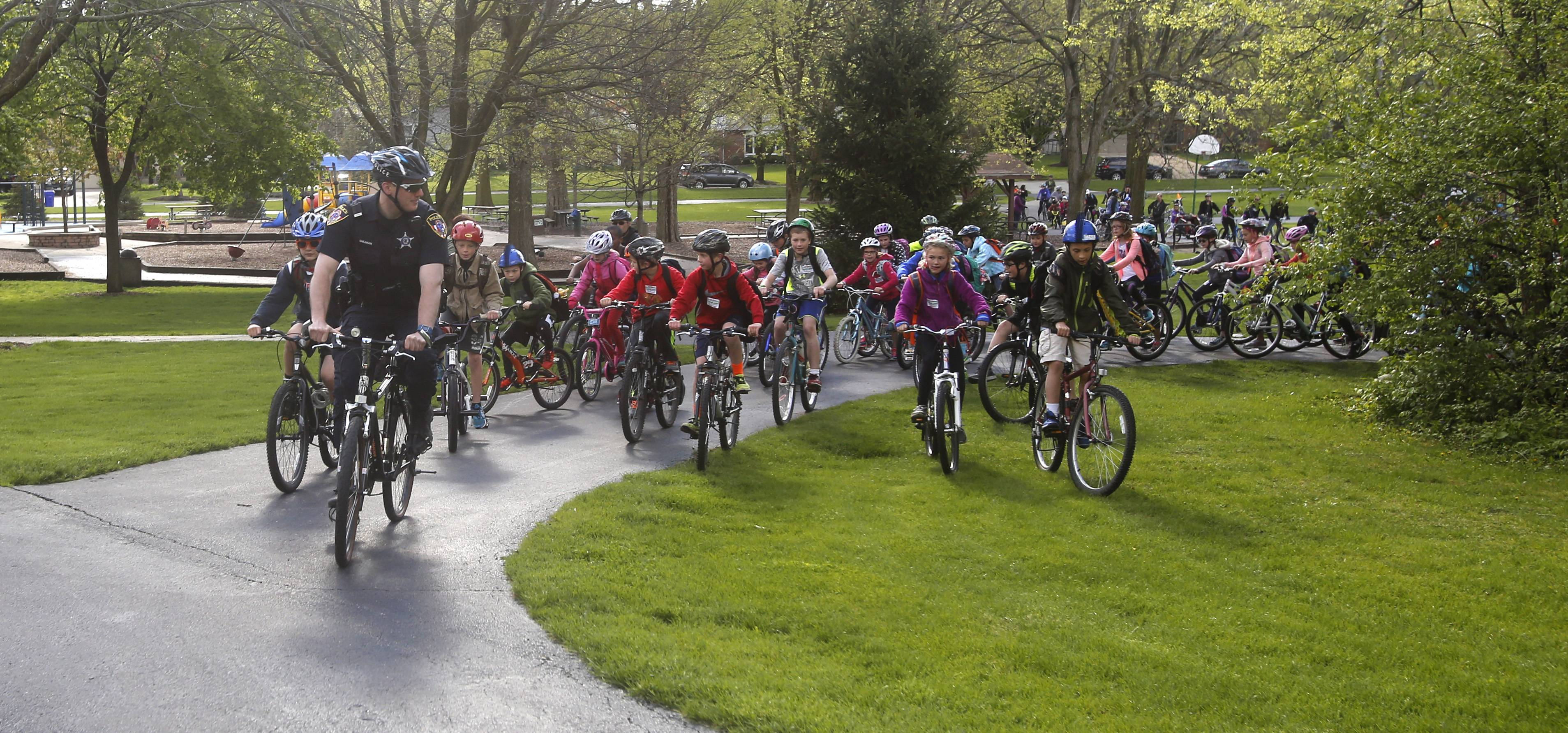 Wheaton Police Officer Mike Sheahan leads students out of Kelly Park during the National Bike to School Day in Wheaton.