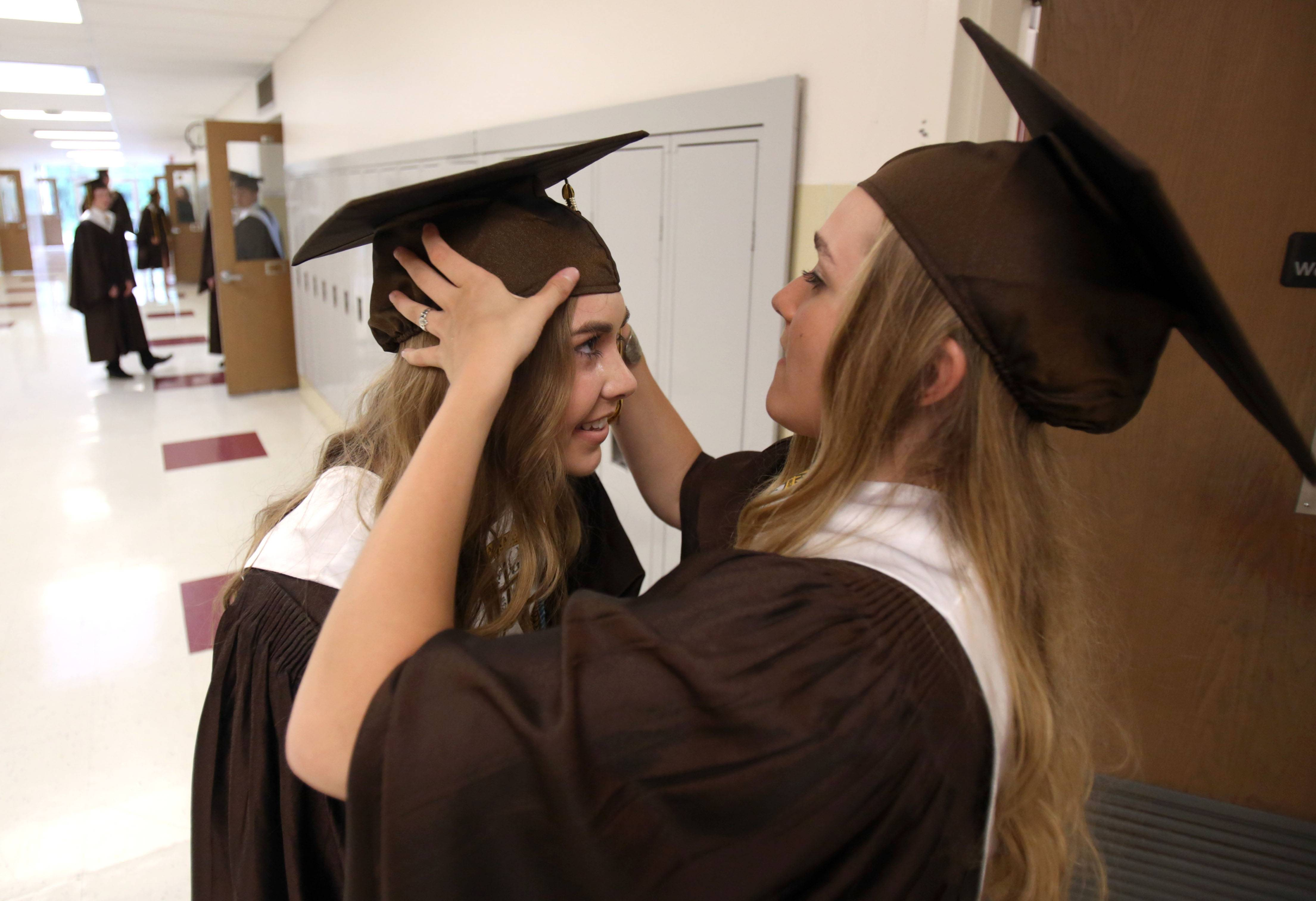 Eva Savovich, right, helps Meeghan Paslaski with her cap.