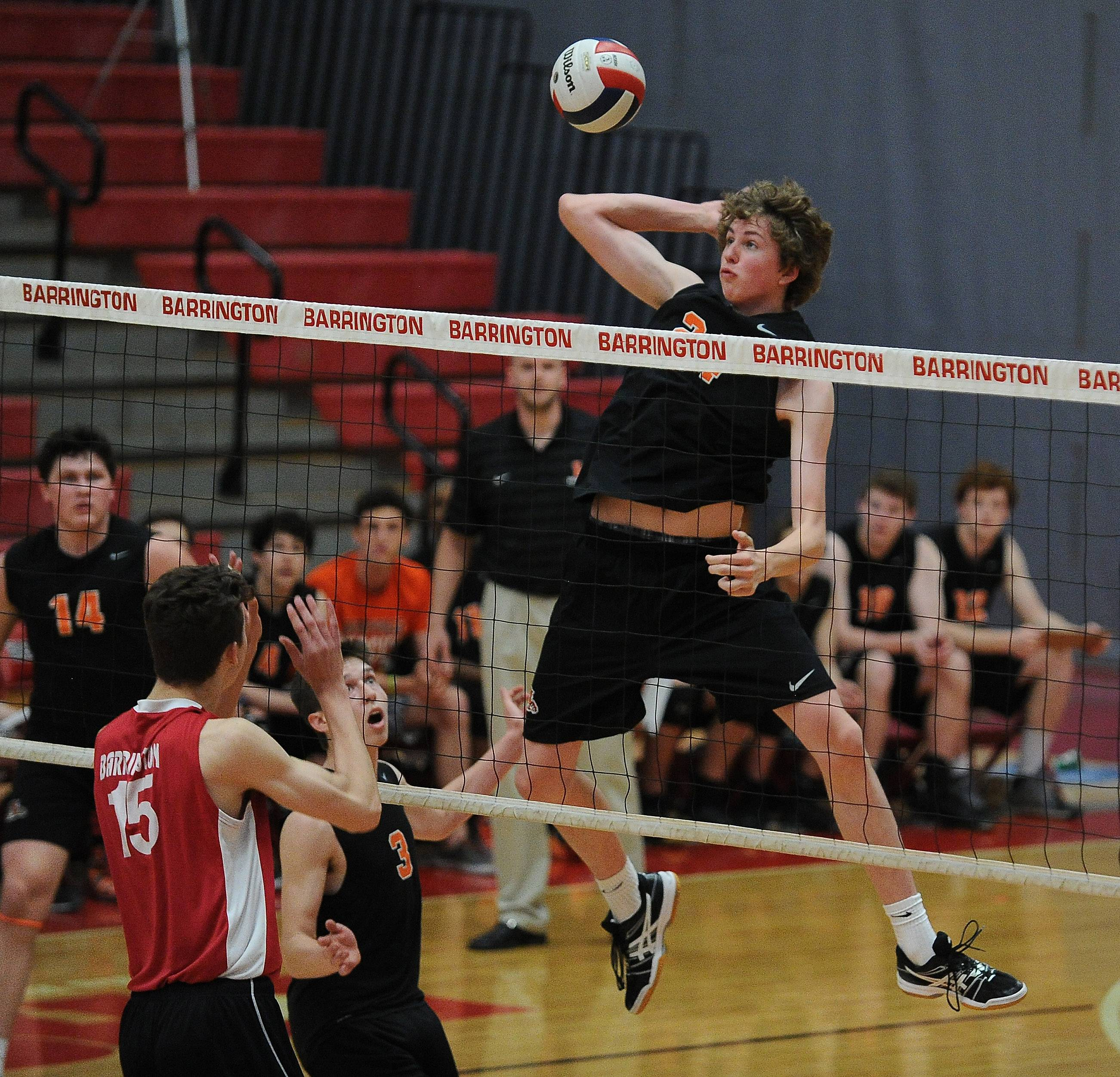 Libertyville's Shane Feiereisel gains height to slam one past Barrington's T. J. Murray in sectional semifinal play at Barrington High School on Friday.