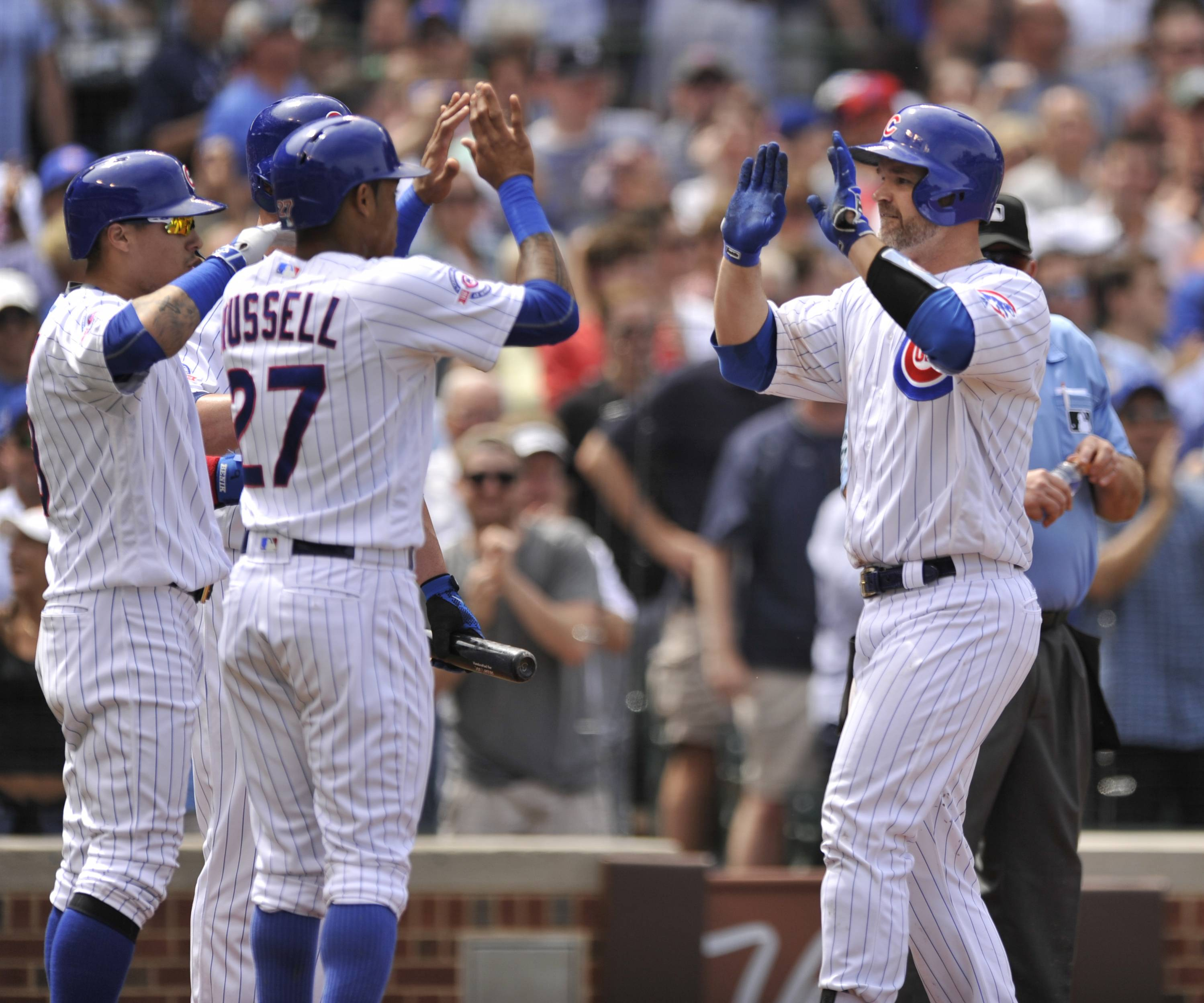 Chicago Cubs' David Ross right, celebrates with teammates Addison Russell, Javier Baez left, and Jon Lester, at home plate after hitting a three-run home run during the fourth inning against the Philadelphia Phillies, Friday in Chicago. It was Ross' 100th career home run.