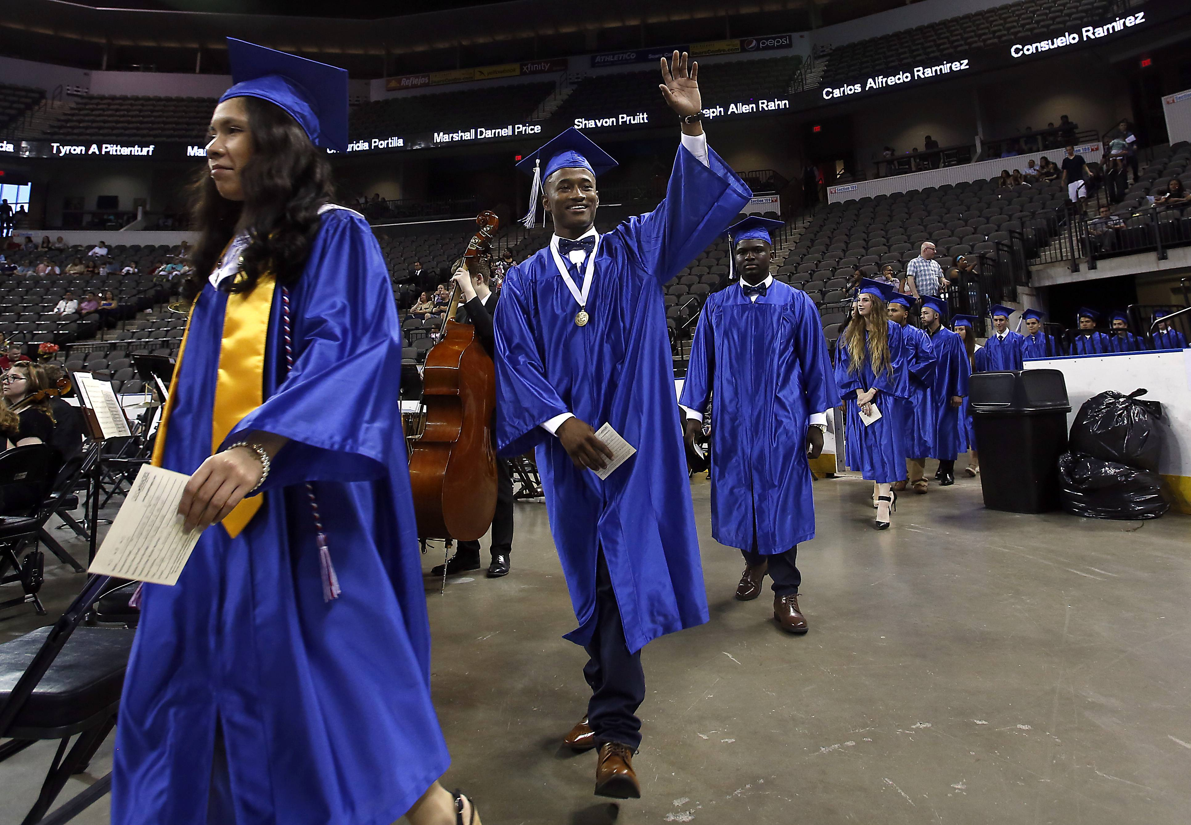Deion Adams, 18, waves to his family during the Larkin High School graduation, Saturday at the Sears Centre in Hoffman Estates.