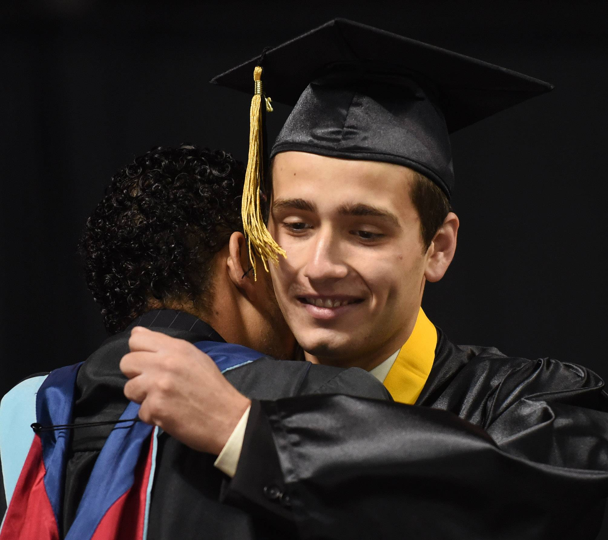 Valedictorian Theofilos Lolis hugs Principal Ariel Correa as he is introduced during the Streamwood High School graduation at the Sears Centre in Hoffman Estates Saturday.
