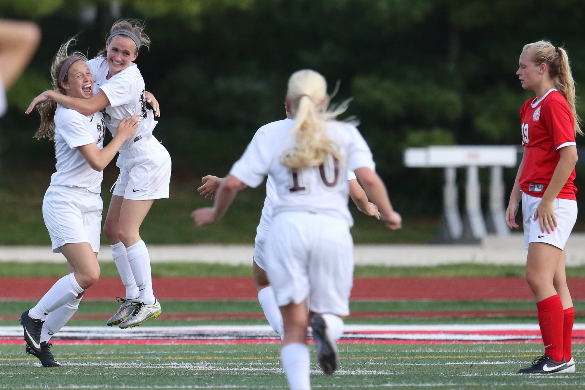 Wheaton Academy forward Gretchen Pearson (left) gives forward Sophie Lindquist (14) a hug after Sophie scores a goal in overtime against Marian Central during the girls Class 1A championship soccer game at North Central College in Naperville, IL on Saturday, May 28, 2016