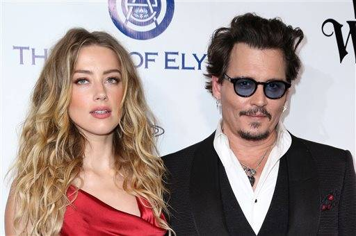 FILE - In this Jan. 9, 2016 file photo, Amber Heard, left, and Johnny Depp arrive at The Art of Elysium's Ninth annual Heaven Gala at 3LABS, in Culver City, Calif. Heard was in Los Angeles Superior Court court on Friday, May 27, 2016, and provided a sworn declaration that her husband Johnny Depp threw her cellphone at her during a fight Saturday, striking her cheek and eye. The judge ordered Depp to stay away from his estranged wife and ruled that Depp shouldn't try to contact Heard until a hearing is conducted on June 17. Heard filed for divorce on Monday. (Photo by Rich Fury/Invision/AP, File)