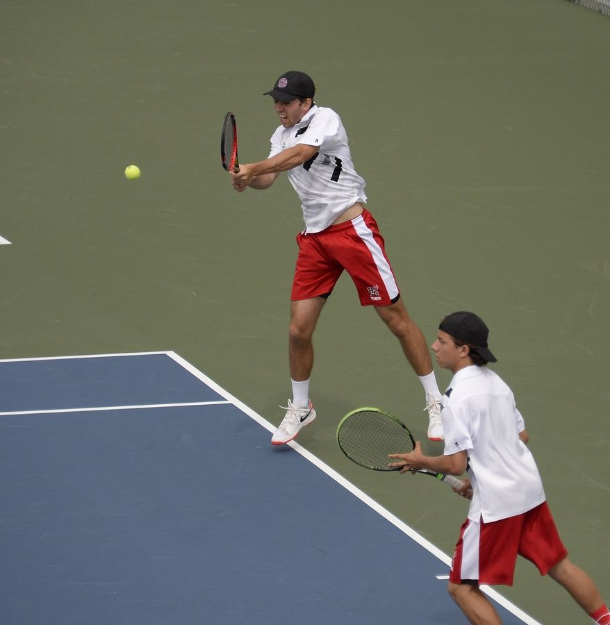 Hinsdale Central's Nick Calzolano returns a slam as teammate Michael Czlonka looks on in doubles semifinal play at Hersey on Saturday.