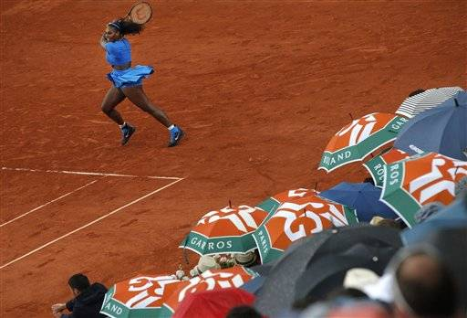 Spectators shield themselves from the rain as Serena Williams of the U.S. returns in the third round match of the French Open tennis tournament against France's Kristina Mladenovic at the Roland Garros stadium in Paris, France, Saturday, May 28, 2016. (AP Photo/Christophe Ena)