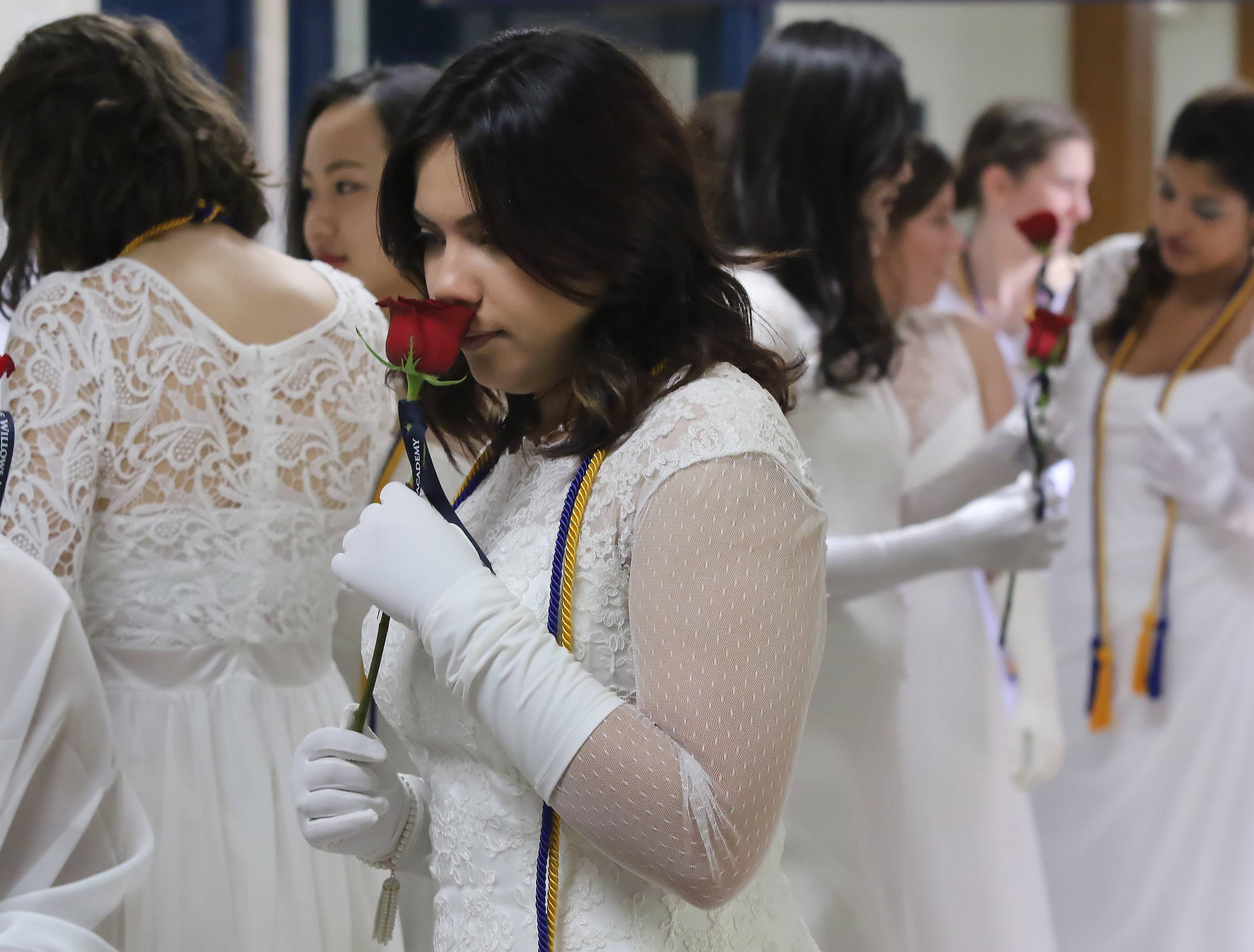 Sarah Maywald smells a rose she received before the graduation ceremony at The Willows Academy in Des Plaines on Sunday. There were 43 graduates at this year's commencement exercises.