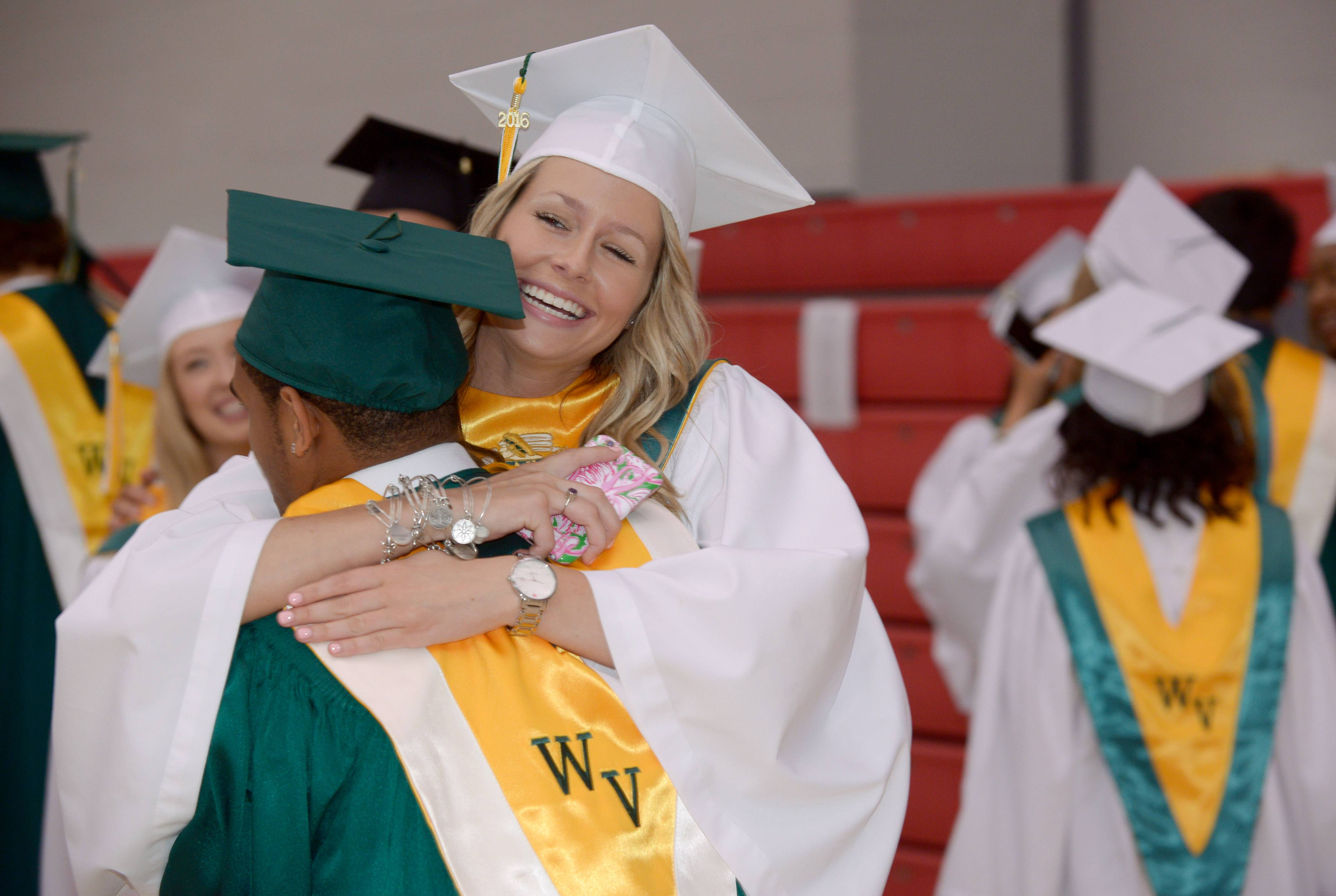 Lauren Howard give Rodney Gee a big hug before the start of the Waubonsie Valley High School graduation ceremony at Northern Illinois University in DeKalb on May 29, 2016.