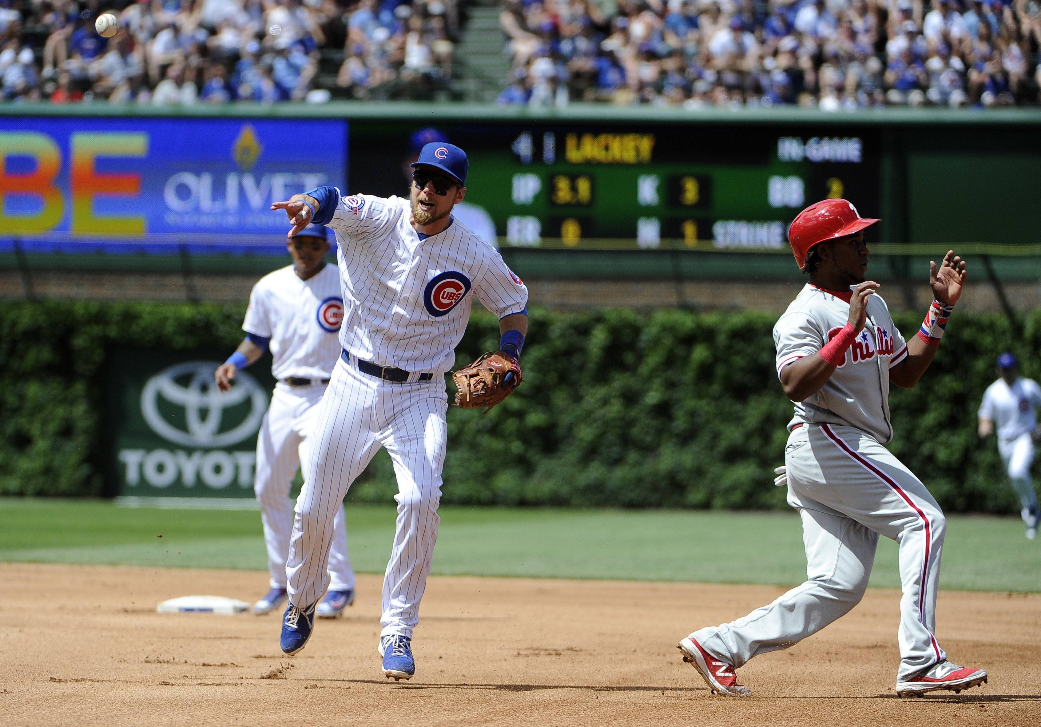 Chicago Cubs second baseman Ben Zobrist, front left, throws to first base to get Philadelphia Phillies' Tommy Joseph in a double play as Phillies' Maikel Franco, right, runs out of the base line during the fourth inning of a baseball game, Sunday, May 29, 2016, in Chicago. (AP Photo/David Banks)