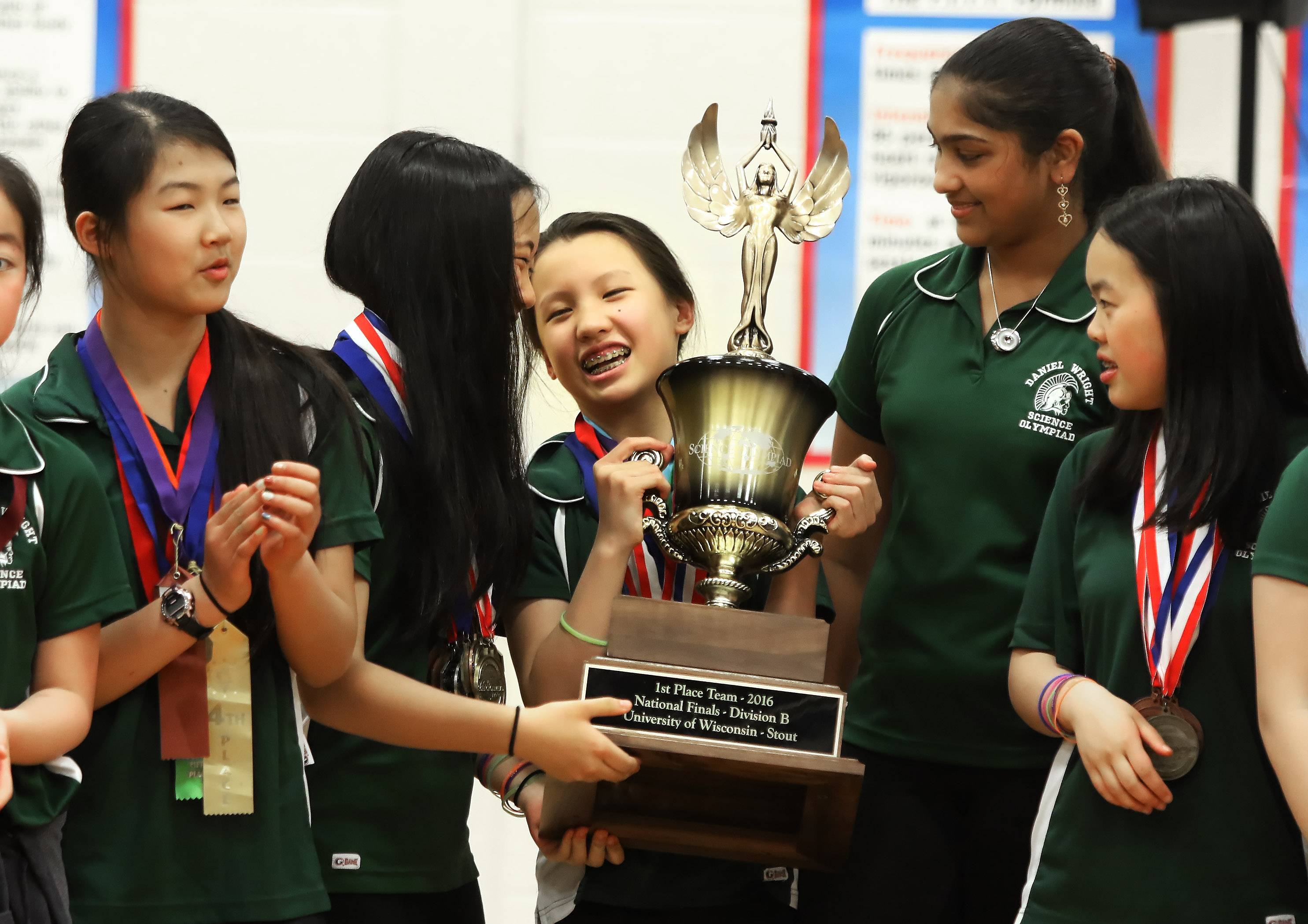 Wright Junior High School sixth-grader Anna Cai and Hannah Liu, left, hold the national trophy won by the school's Science Olympiad team during an assembly at the Lincolnshire school.