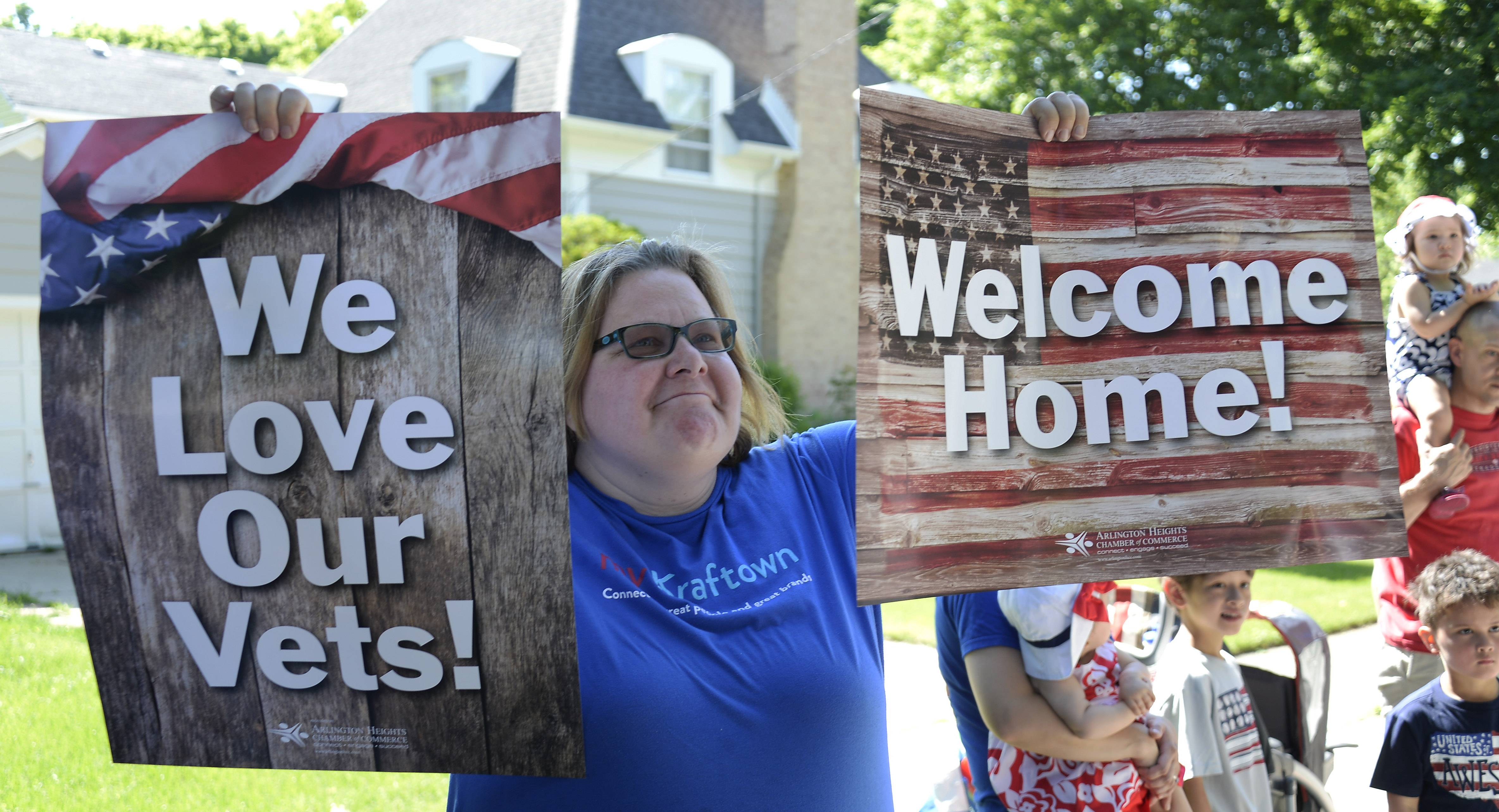 Ann Berrie of Arlington Heights holds up signs reflecting the village's gratitude to its veterans as they stream by Monday in the Arlington Heights Memorial Day parade.