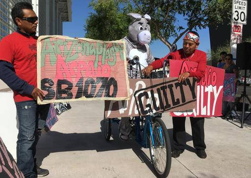 Protestors carry signs in protest of Sheriff Joe Arpaio outside the federal courthouse in Phoenix, Ariz. on Tuesday, May 31, 2016. A federal judge will hold a hearing Tuesday to examine ways to address the Maricopa County sheriff's contempt-of-court violations in a racial profiling case. Arpaio was found in civil contempt two weeks ago for disobeying court orders in the profiling case, including letting his immigration patrols continue after the judge ordered them stopped.