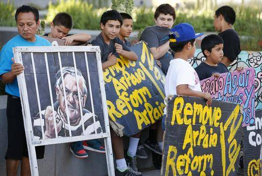 FILE - In this Wednesday, May 25, 2016 file photo, protesters rally in front of Maricopa County Sheriff's Office Headquarters in Phoenix. Arizona taxpayers could be paying out to compensate hundreds of Latinos who were illegally detained when Sheriff Joe Arpaio rounded them up in past immigration patrols. A federal judge will hold a hearing Tuesday, May 31, 2016, to examine ways to address the Maricopa County sheriff???s contempt-of-court violations in a racial profiling case. Sheriff Joe Arpaio was found in civil contempt two weeks ago for disobeying court orders in the profiling case, including letting his immigration patrols continue after the judge ordered them stopped.
