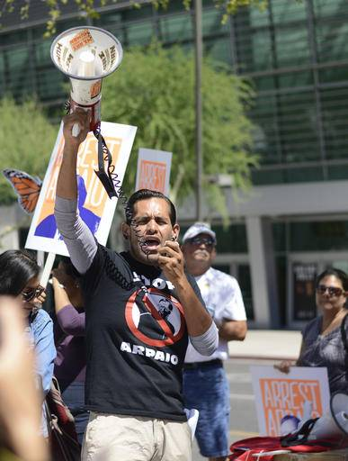 An activist leads chants with protesters outside the federal courthouse where Arizona Sheriff Joe Arpaio is appearing before a judge, on Tuesday, May 31, 2016, in Phoenix, Ariz. A judge considering penalties against Maricopa County Sheriff Arpaio for contempt-of-court violations involving a racial profiling case suggests taxpayers likely will foot the bill for the lawman's intentional disobedience. U.S. District Judge Murray Snow was holding a hearing Tuesday to examine responses to the civil contempt violations of Arpaio that included letting his immigration patrols proceed 18 months after the judge ordered them stopped.