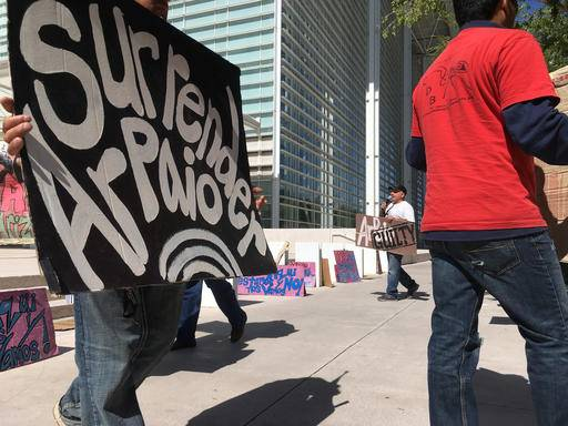 Protestors carry signs in protest of Arizona Sheriff Joe Arpaio outside the federal courthouse in Phoenix, Ariz. on Tuesday, May 31, 2016. A federal judge will hold a hearing Tuesday to examine ways to address the Maricopa County sheriff's contempt-of-court violations in a racial profiling case. Arpaio was found in civil contempt two weeks ago for disobeying court orders in the profiling case, including letting his immigration patrols continue after the judge ordered them stopped.