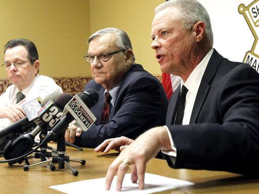 FILE - In this Dec. 5, 2011 file photo, Maricopa County Sheriff Joe Arpaio, center, listens as Chief Deputy Jerry Sheridan, right, discusses the latest in the document release on his office's handling of many sexual assault cases over the years in El Mirage, Ariz., during a news conference in Phoenix. A federal judge will hold a hearing Tuesday, May 31, 2016, to examine ways to address the Maricopa County sheriff's contempt-of-court violations in a racial profiling case. Arpaio was found in civil contempt two weeks ago for disobeying court orders in the profiling case, including letting his immigration patrols continue after the judge ordered them stopped. Lawyers who pressed the case against Arpaio are urging the judge to recommend a criminal investigation against the sheriff and his second-in-command, Sheridan.