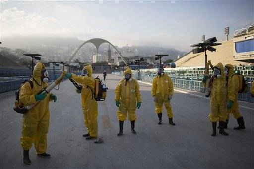 FILE - This is a Tuesday, Jan. 26, 2016 file photo of health workers as they get ready to spray insecticide to combat the Aedes aegypti mosquitoes that transmits the Zika virus under the bleachers of the Sambadrome in Rio de Janeiro, which will be used for the Archery competition in the 2016 summer games. With the opening ceremony just over two months away, Olympic leaders have plenty of challenges to discuss this week when they meet for the last time before gathering in Rio de Janeiro on the eve of South America's first games. (AP Photo/Leo Correa, File)
