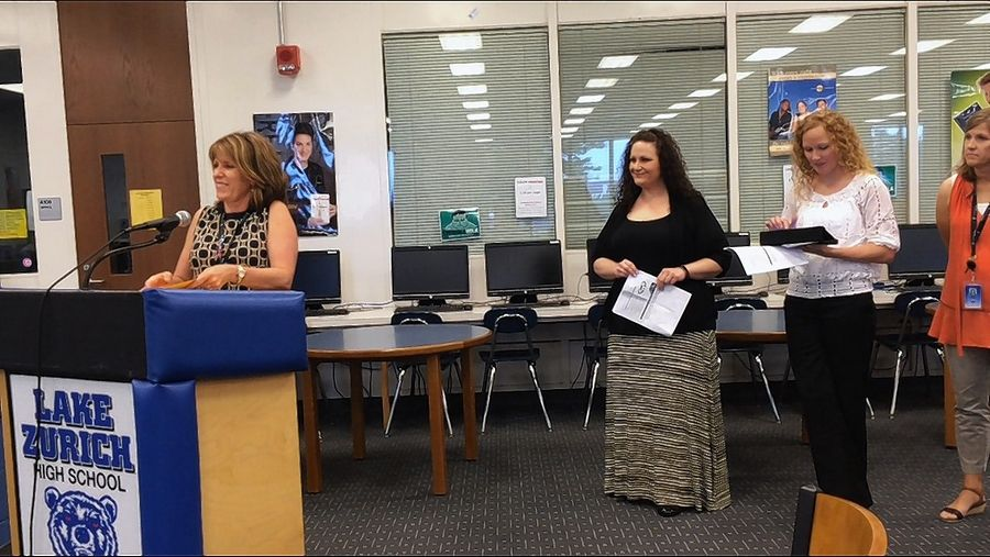 Lake Zurich Unit District 95's assistant superintendent for curriculum and instruction, Jodi Wirt, at podium, speaks about new instructional coaches at a school board meeting. In background to the right of Wirt are coaches Jill Nagle, Capri Paluch and Carrie Collins.