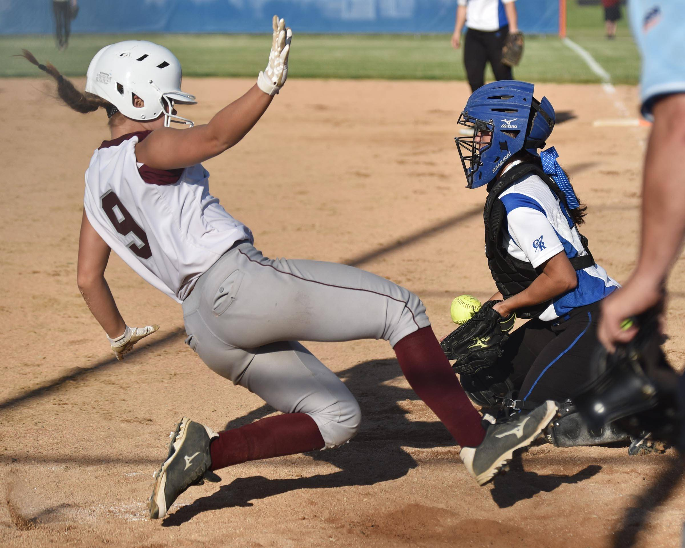 Marengo's Susannah Nawrot scores the only run of the game in the 10th inning as Burlington Central catcher Kelly Wiater tries to handle a late throw Wednesday in the Class 3A Genoa-Kingston sectional semifinal.