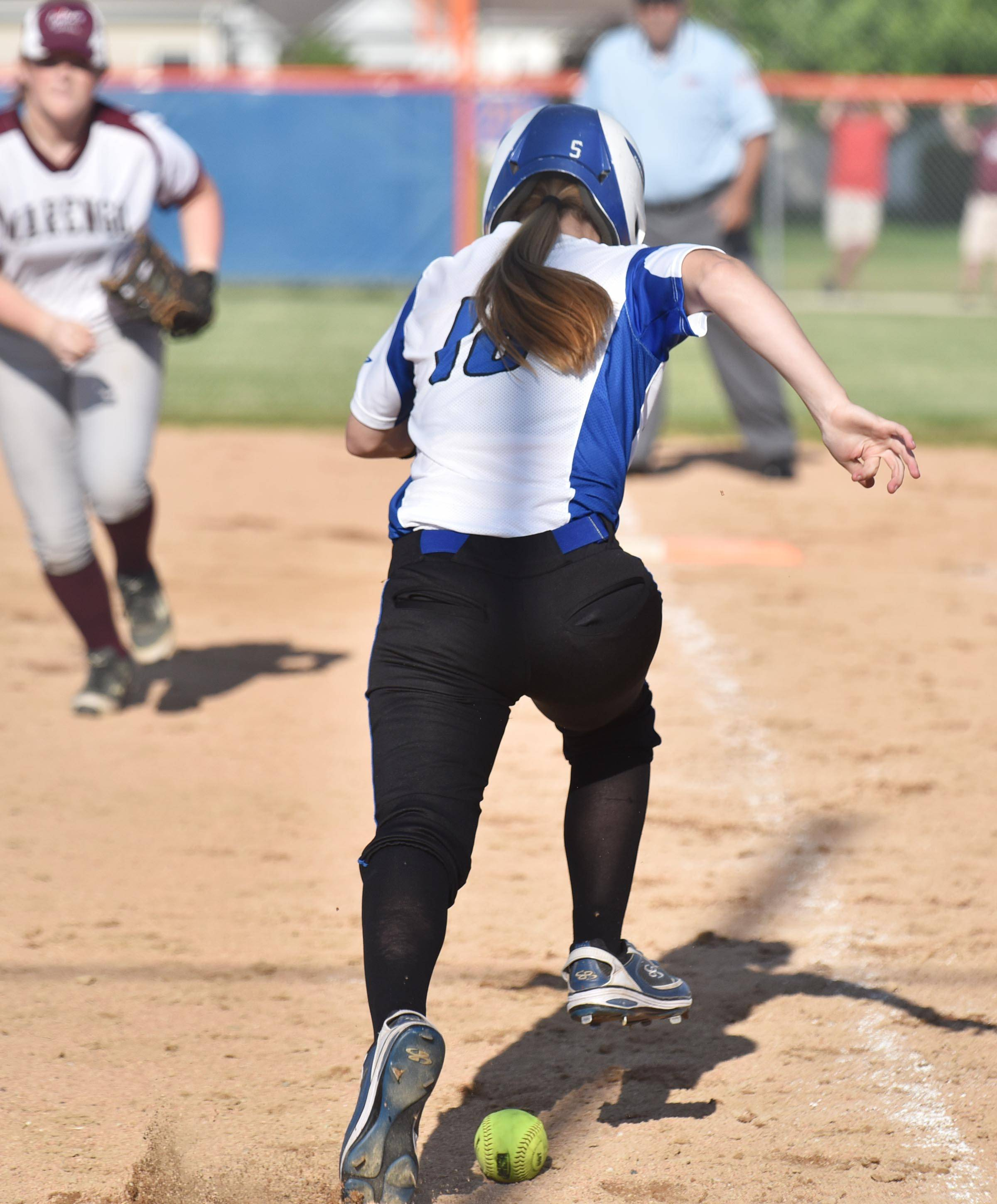 Burlington Central's Sarah Kinney steps over her bunted ball as she safely scampers to first base against Marengo Wednesday in the Genoa-Kingston sectional game.