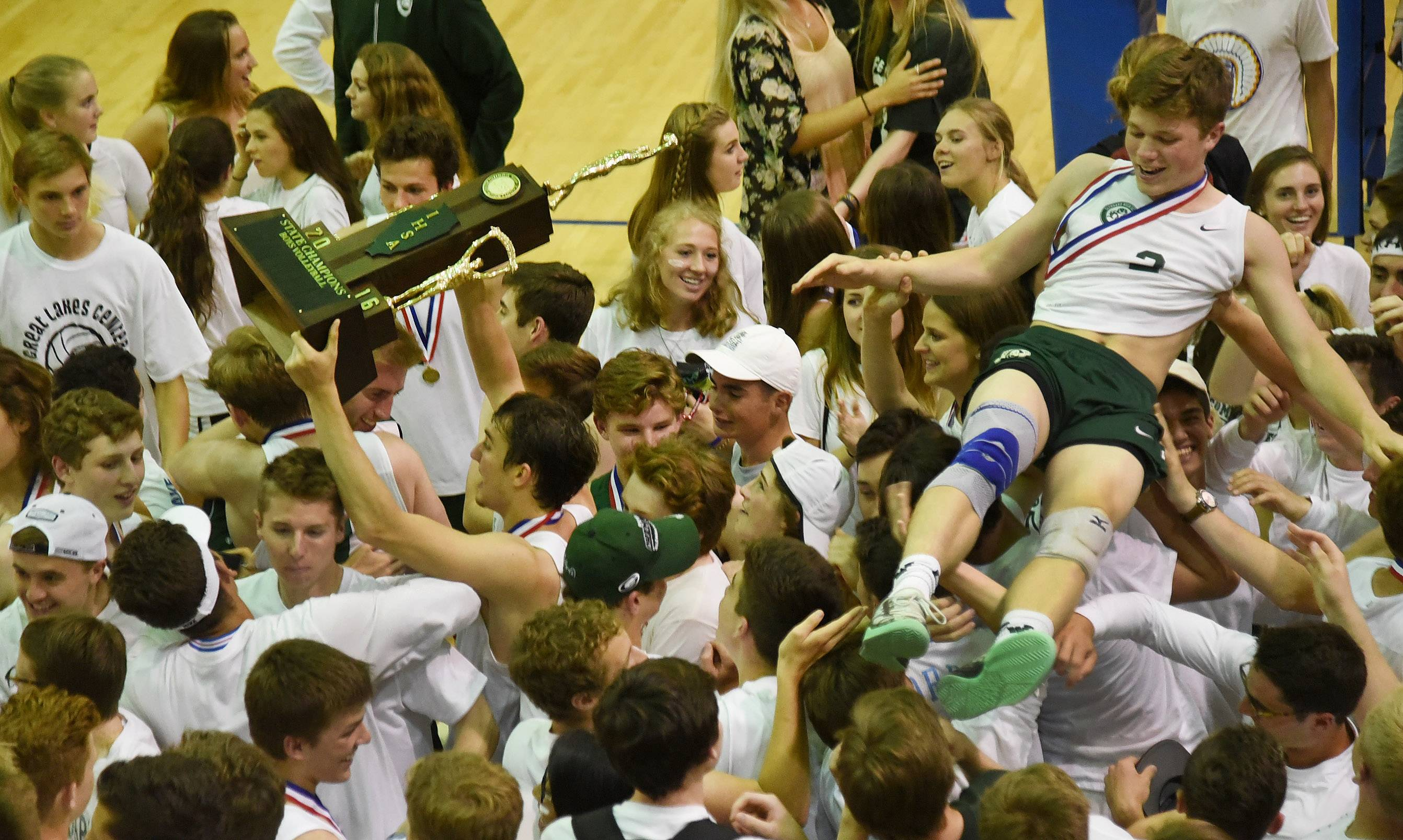 Kyler Kotsakis hoists the trophy, while Eric Shanahan body surfs as Glenbard West celebrates the boys volleyball, state championship after defeating New Trier.