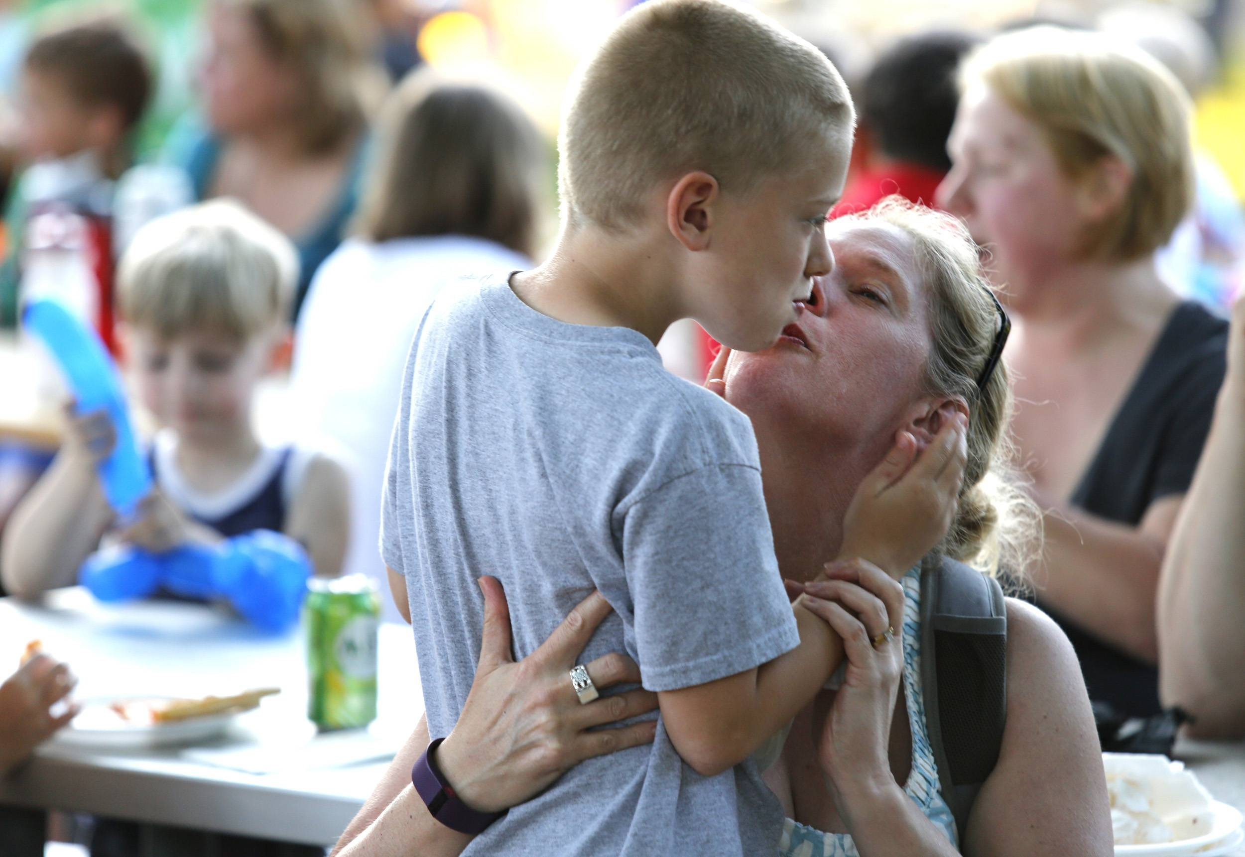 Heather Wise, of Glen Ellyn gets a kiss from her son Gunnar Wise, 7, during Taste of Wheaton in Memorial Park.