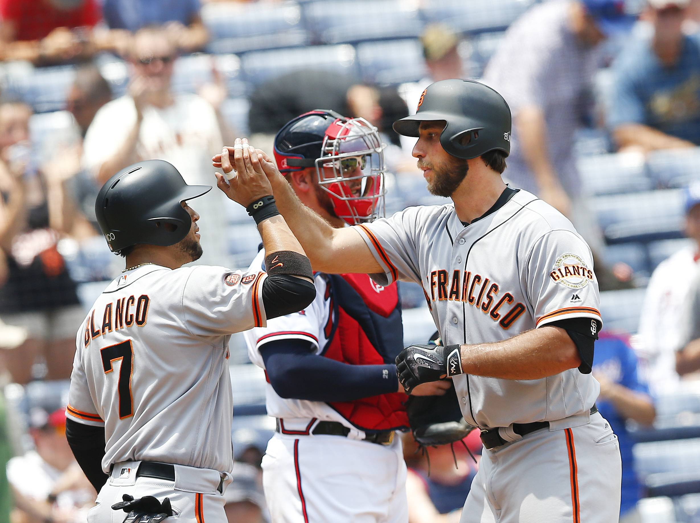 San Francisco Giants starting pitcher Madison Bumgarner, right, celebrates with Gregor Blanco (7) after hitting a two-run home run as Atlanta Braves catcher Tyler Flowers looks on in the background in the fifth inning of a baseball game Thursday, June 2, 2016, in Atlanta. (AP Photo/John Bazemore)
