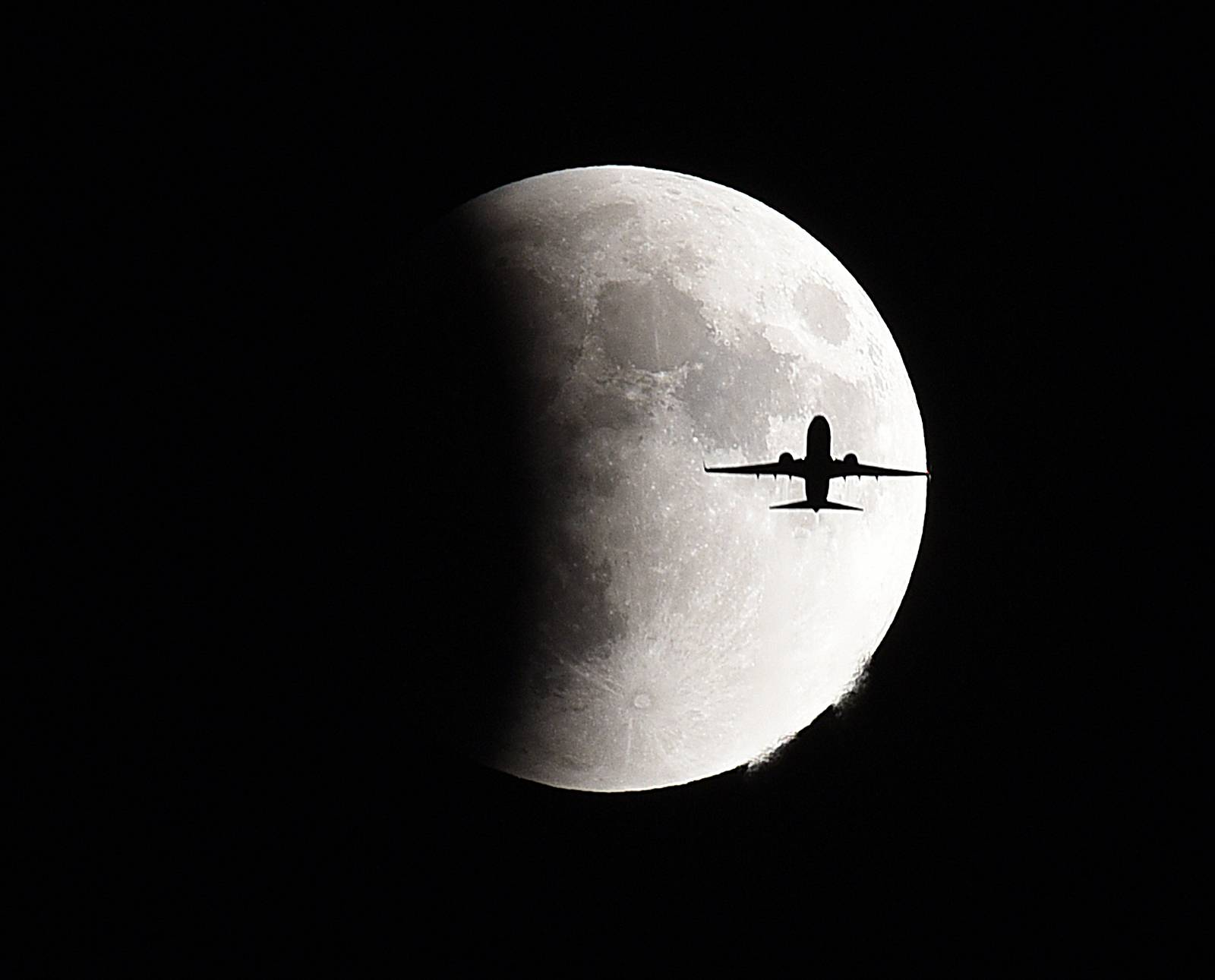 A jet flies in front of the moon during a supermoon lunar eclipse.