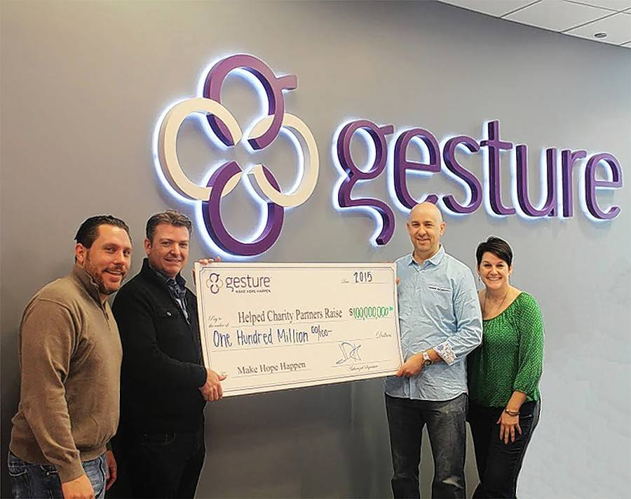 Gesture founder and CEO Jim Alvarez, second from left, celebrates helping charities raise $100 million in 2015 with team members, from left, Steve Greanias, senior vice president of sales and operations, Rich Aquino, chief technology officer, and Dianne Kleber, director of sales.
