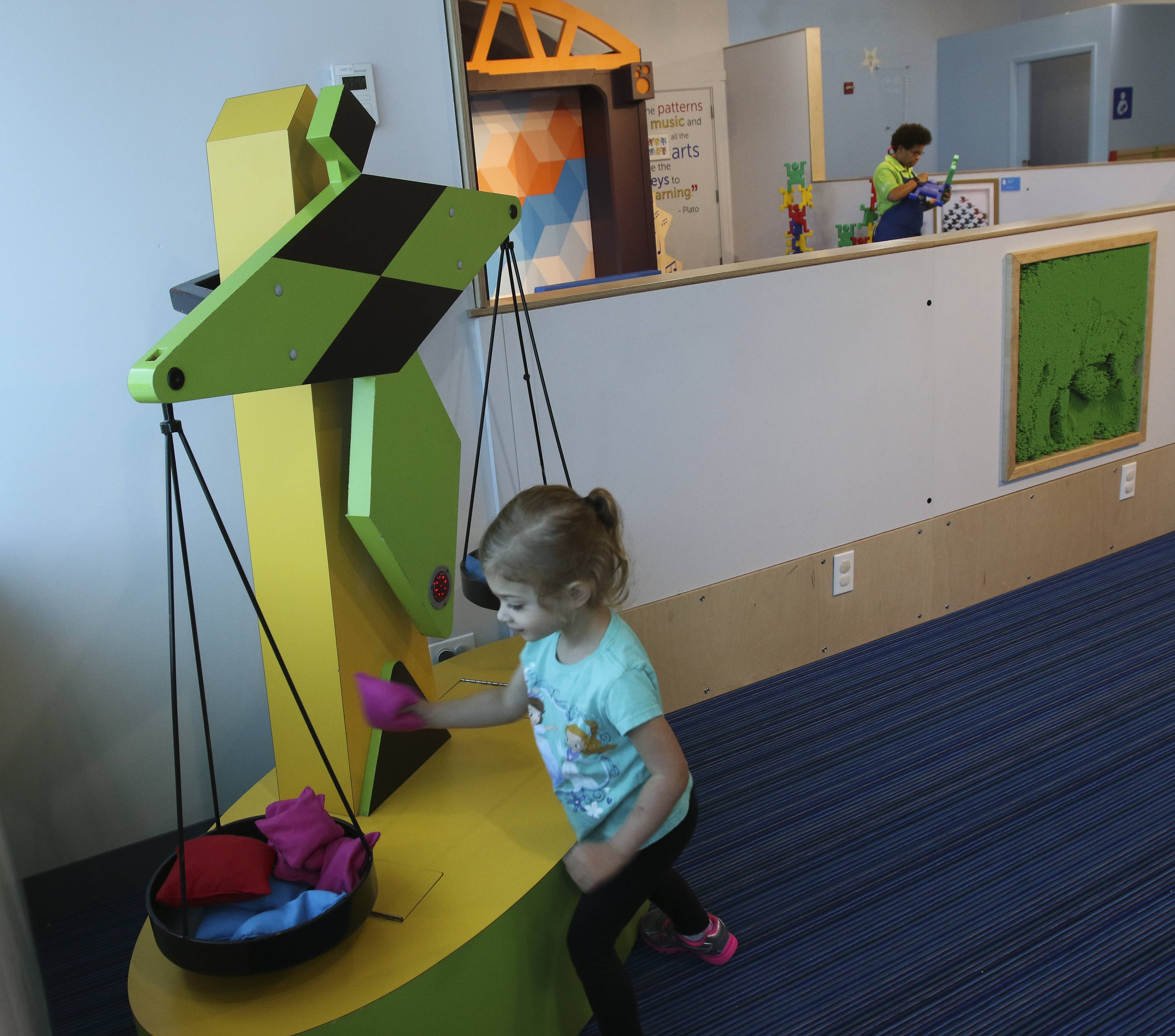 Emily Prothe, 3, of Wheaton, tries out a balance scale at the new Math+Motion exhibit at the DuPage Children's Museum.