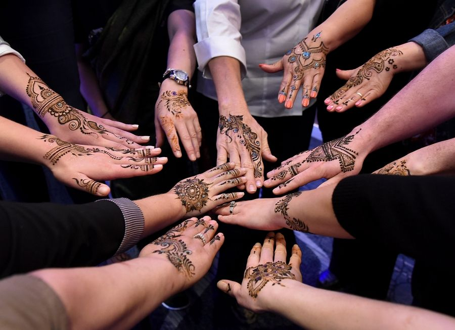 Renaissance Schaumburg employees show off their henna body art, as Marriott International hosts a multicultural training session for employees about Indian weddings.