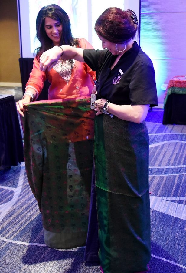 Seema Jain, of Marriott International, shows an employee how to wrap a sari during multicultural training.