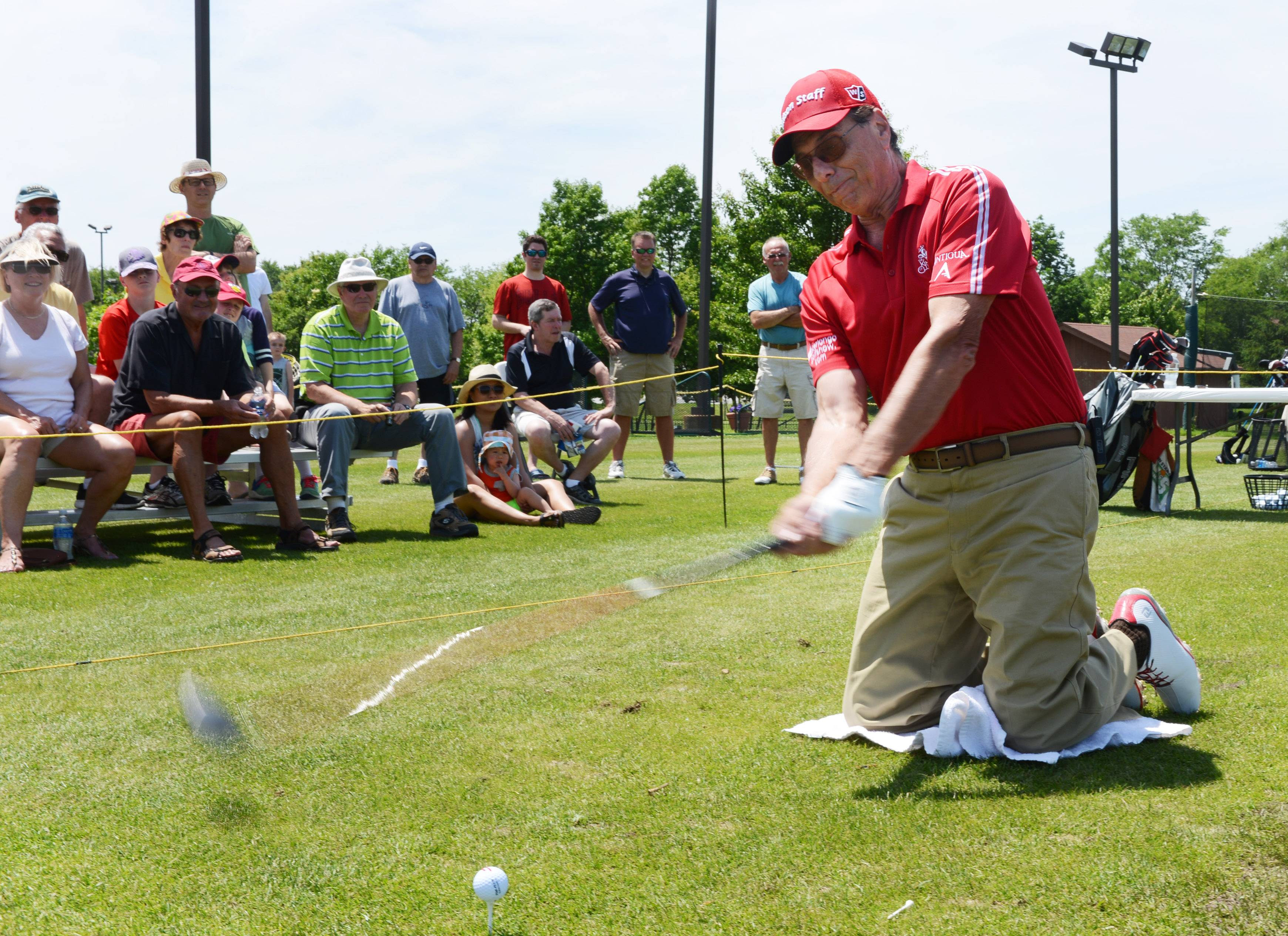 "Local PGA golf professional Peter Longo, ""The King of Clubs,"" performs a golf trick shot with a long driver from his knees as part of Golf Appreciation Day at Links and Tees Golf Facility in Addison Saturday."