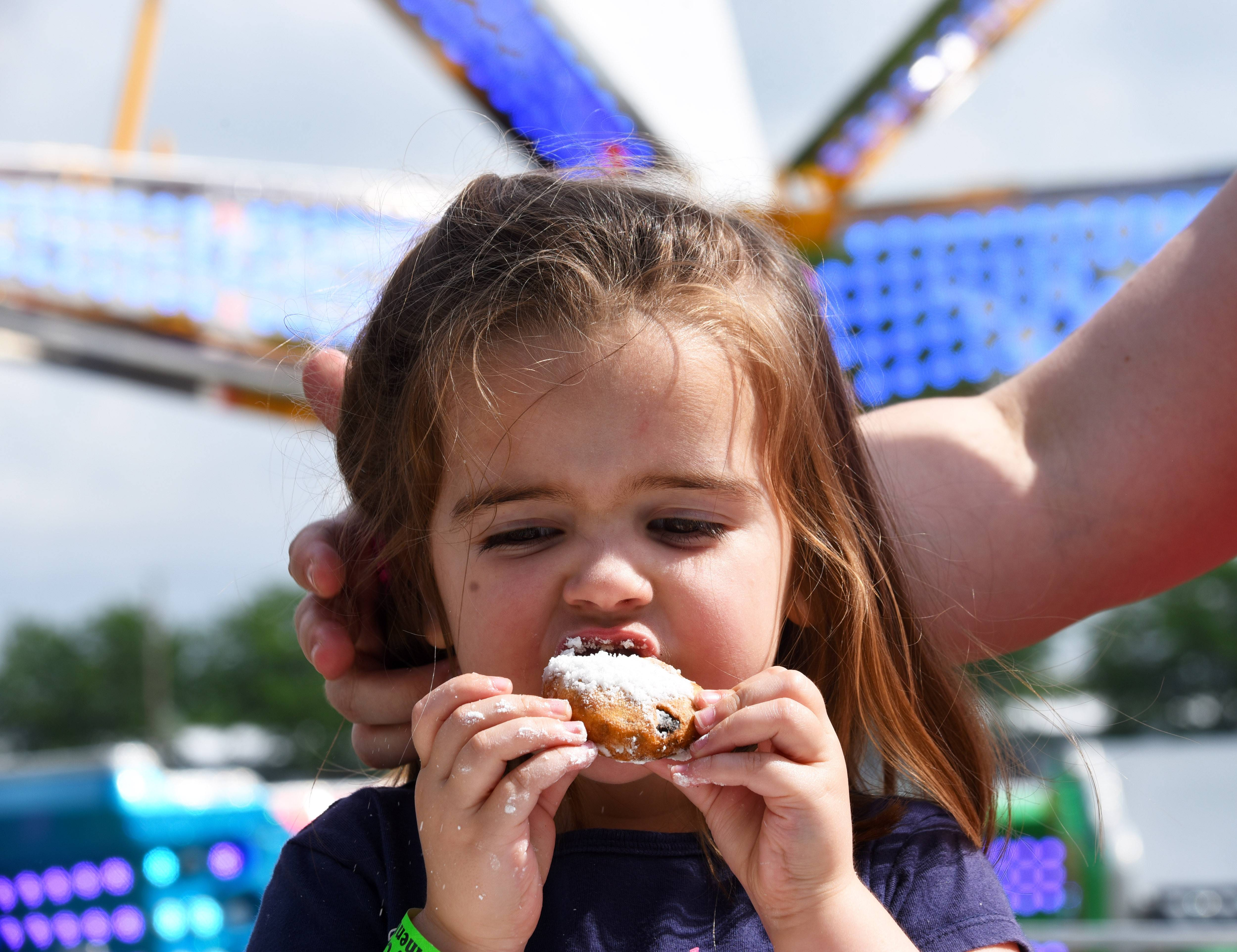 Hayden Michaelis, 3, of St. Charles, tries her first plate of fried oreos while her mother, Katrina Michaelis, keeps her hair out of the way on Saturday at Gilberts Community Days festival in Gilberts. Hayden's father, Eric Michaelis, said it was the family's first time at the carnival and Hayden's favorite part was riding the carousel.