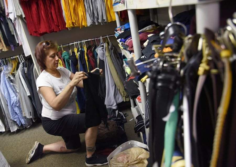 A volunteer at Journeys|The Road Home, a homeless care agency in Palatine, folds donated clothes in their facility at 1140 E. Northwest Hwy. in Palatine.