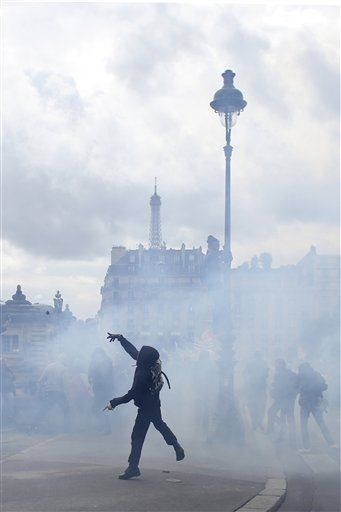 A demonstrators throws objects during a demonstration at the Place des  Invalides in Paris Tuesday, June 14, 2016. Protesters in Paris threw projectiles at police officers, who responded with tear gas, amid demonstrations by tens of thousands of people opposed to a proposed labor law.